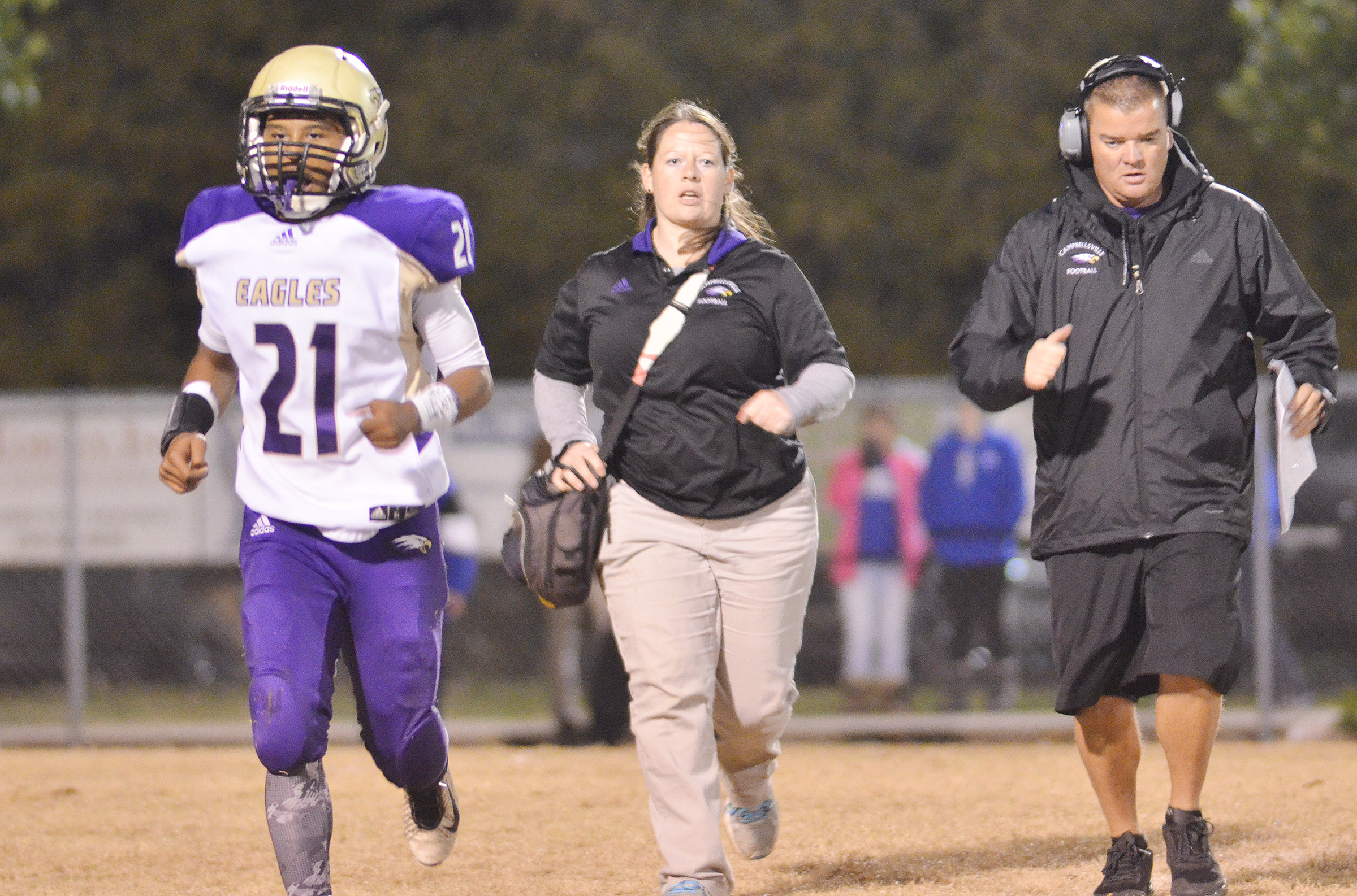 CHS athletic trainer Rebecca Cravens and head coach Dale Estes run back to the sidelines as junior Daesean Vancleave is injured.