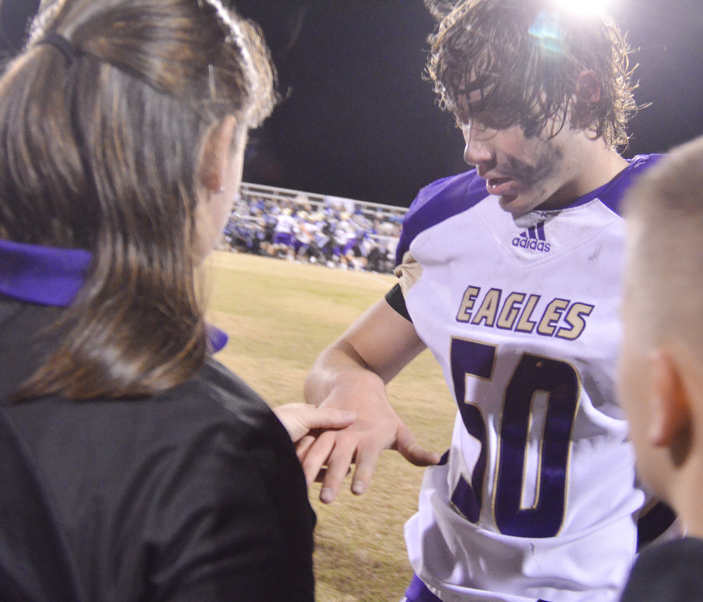 CHS athletic trainer Rebecca Cravens looks at junior Tristan Johnson's hand.