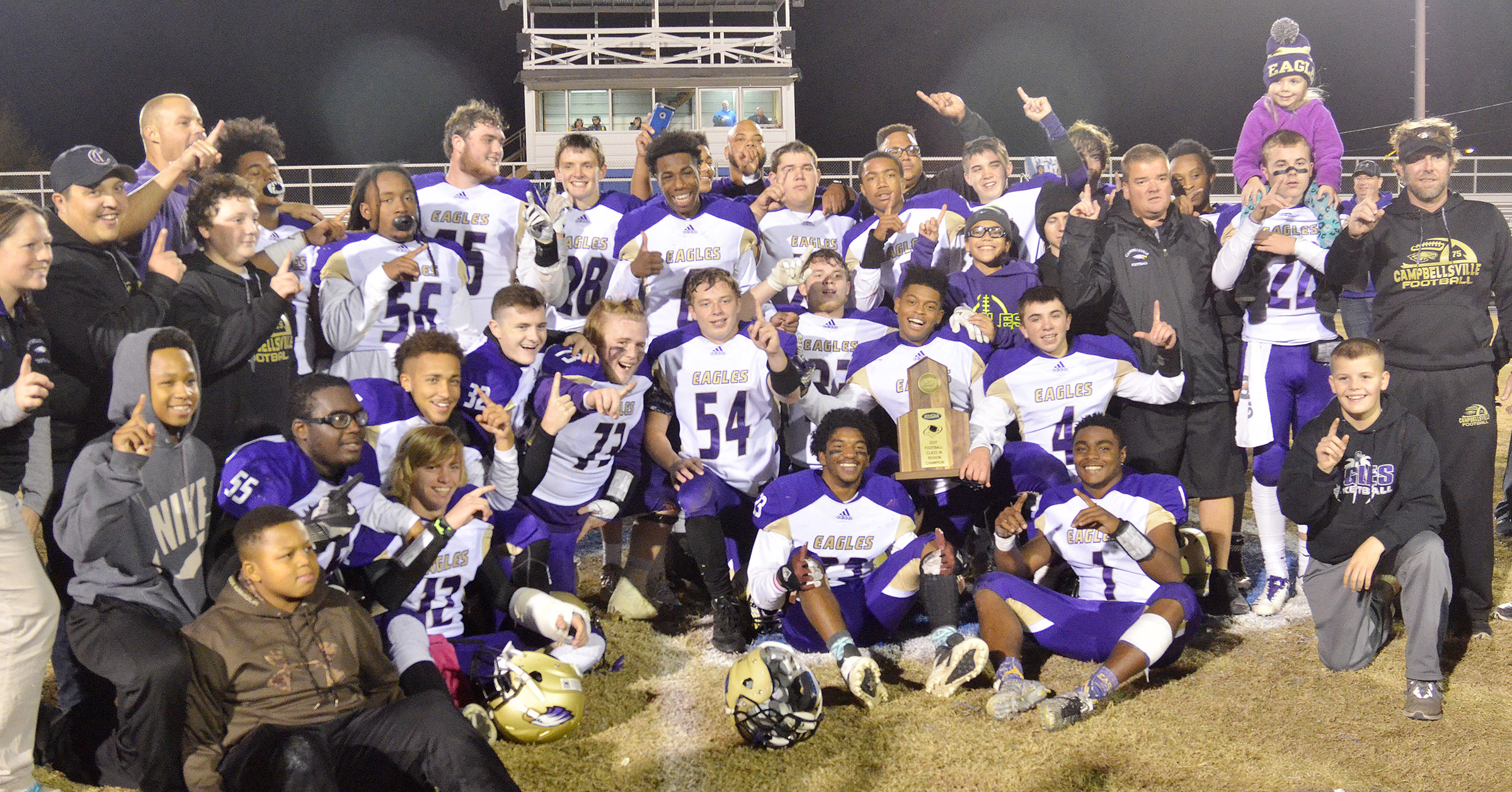 CHS football players and coaches pose for a photo with their region championship trophy.