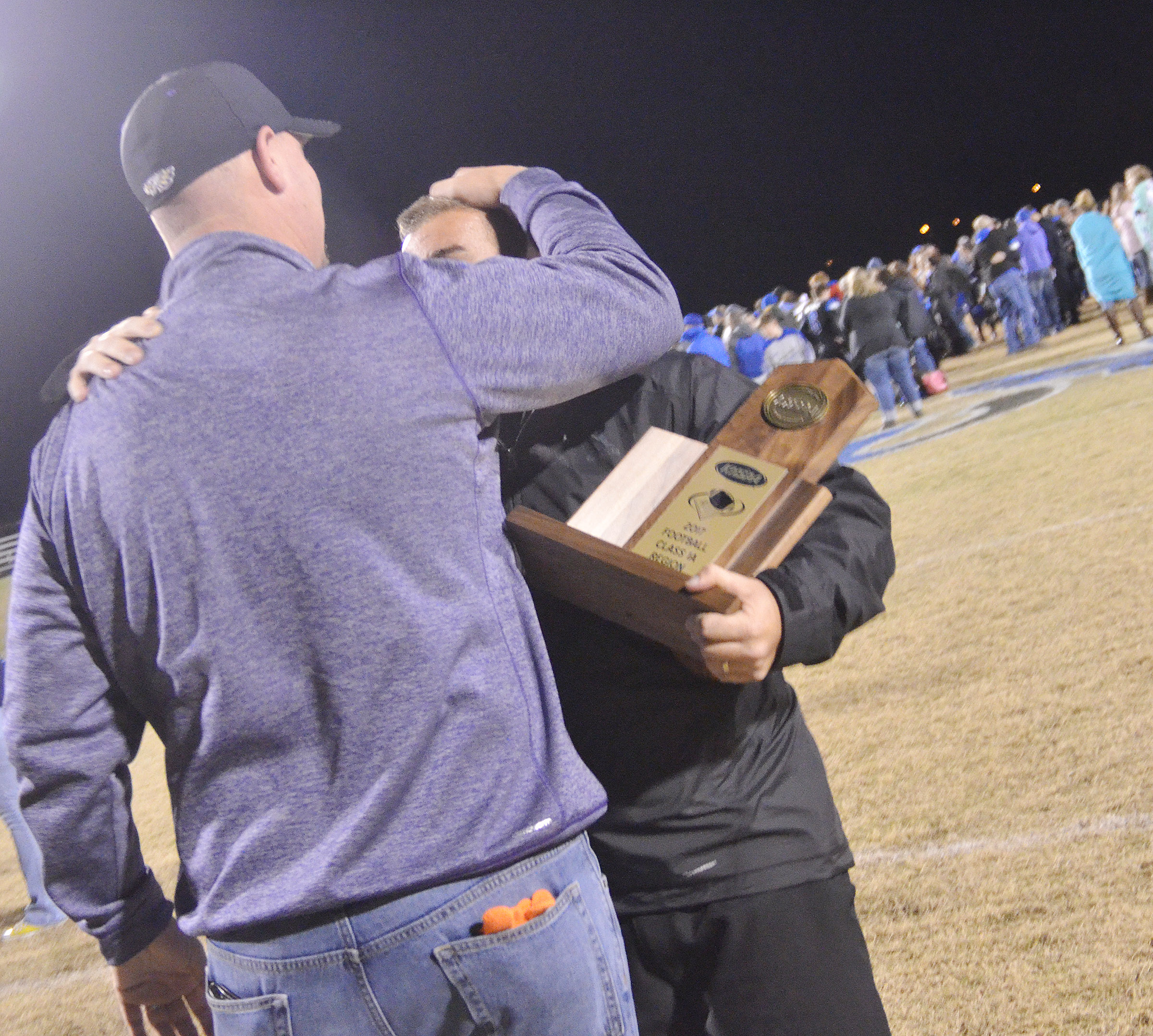 CHS Principal David Petett congratulates head football coach Dale Estes.