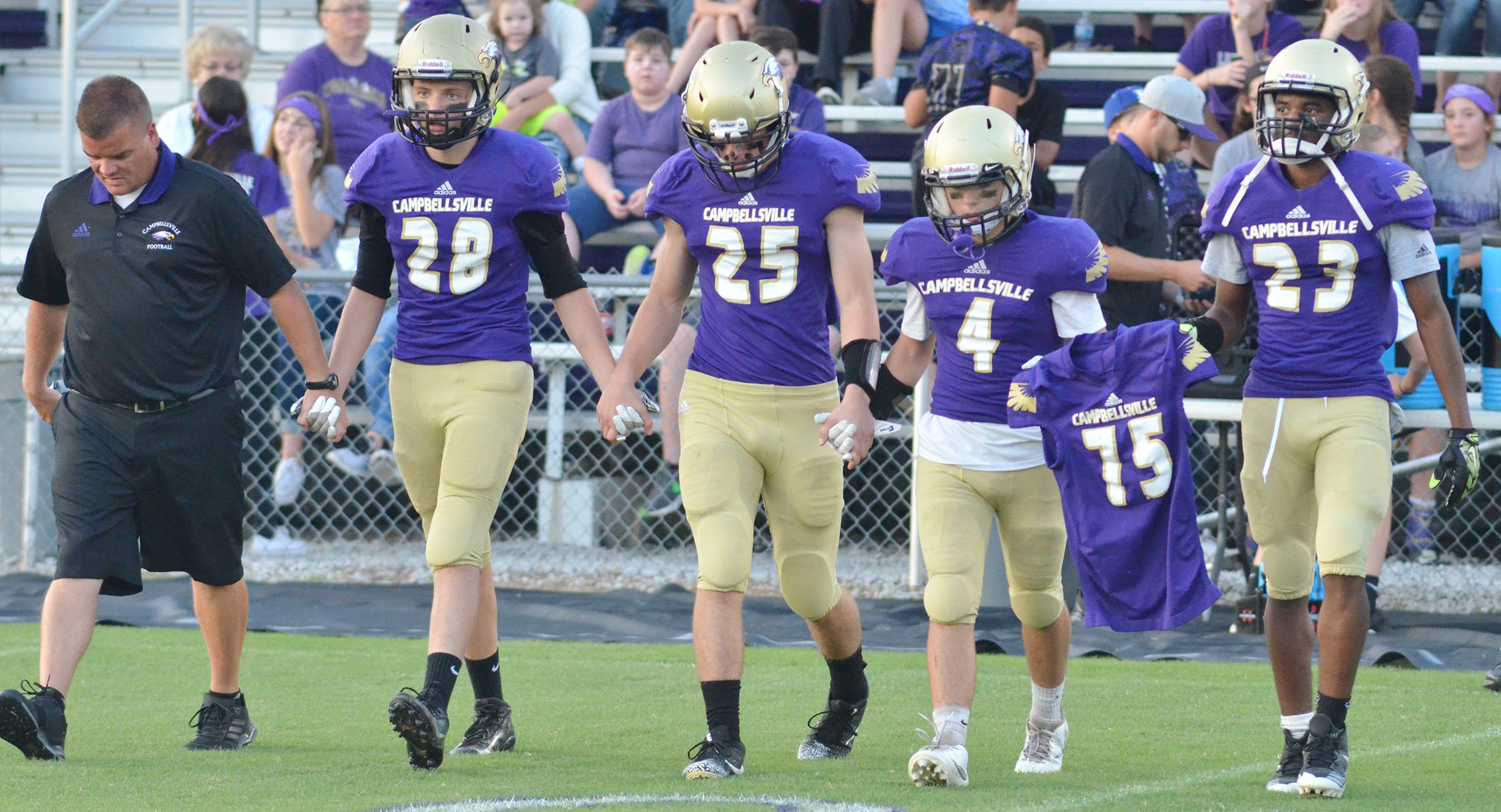 CHS head football coach Dale Estes, at left, lines up with, from left, sophomore Blake Allen, junior Tristan Johnson and seniors Austin Carter and Tyrion Taylor for the coin toss. The players are carrying a jersey in honor of Cameron Smith, who died in 2013 and would have been a senior at CHS this year.