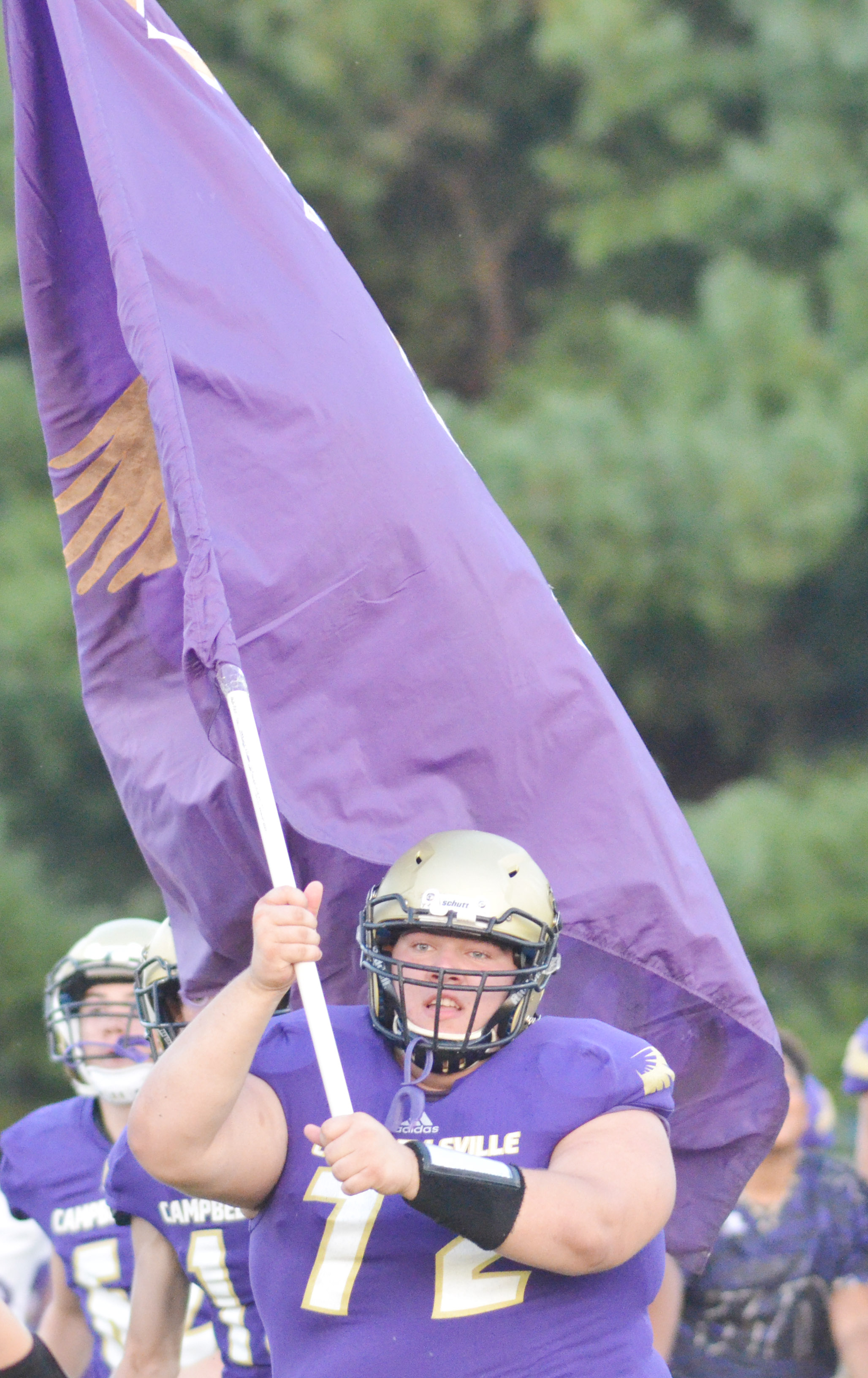 CHS senior Ryan Wiedewitsch carries the Eagles flag onto the field.