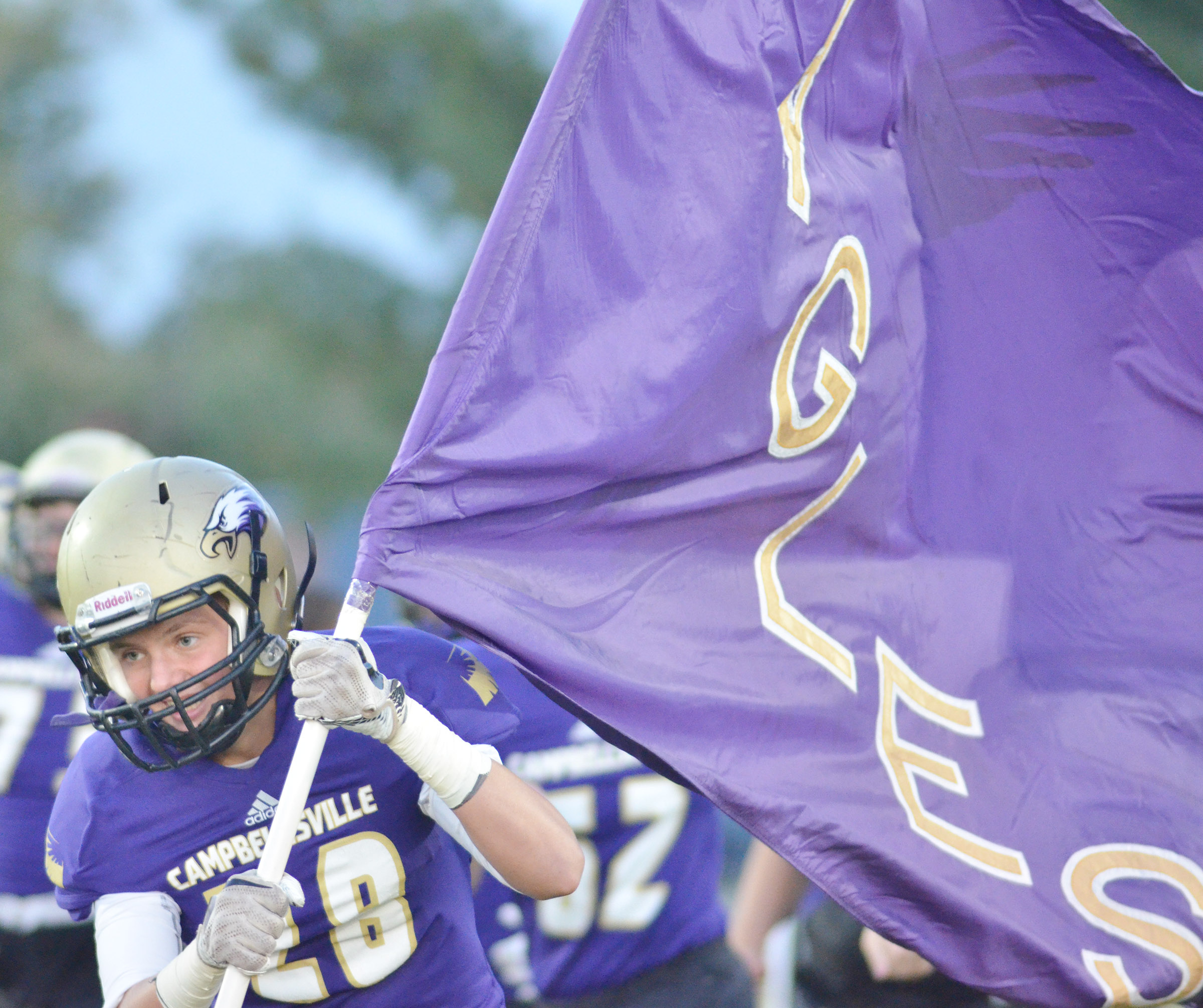 CHS sophomore Blake Allen carries the Eagles flag onto the field.