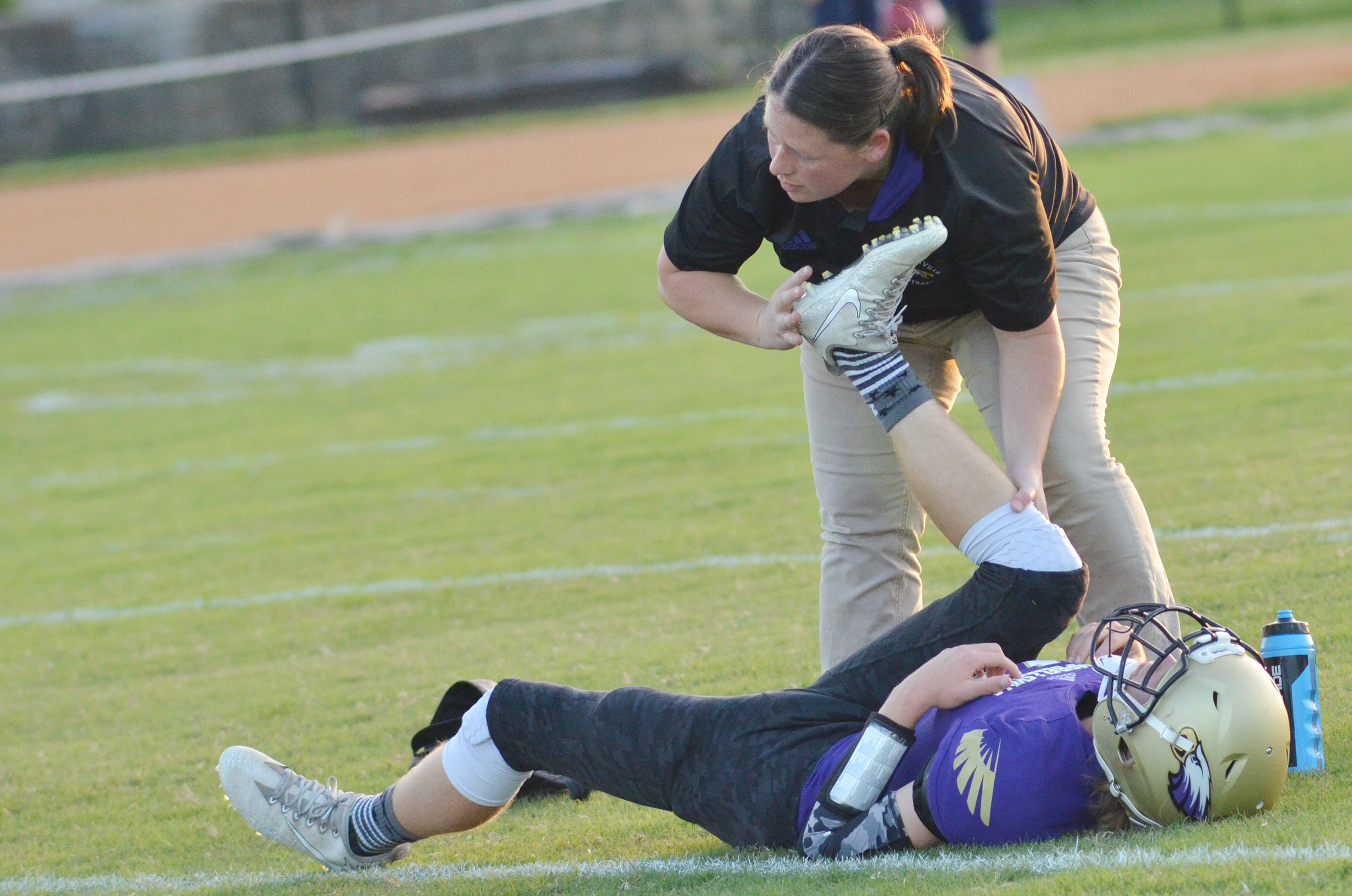CHS trainer Rebecca Cravens stretches with freshman Arren Hash before the game.