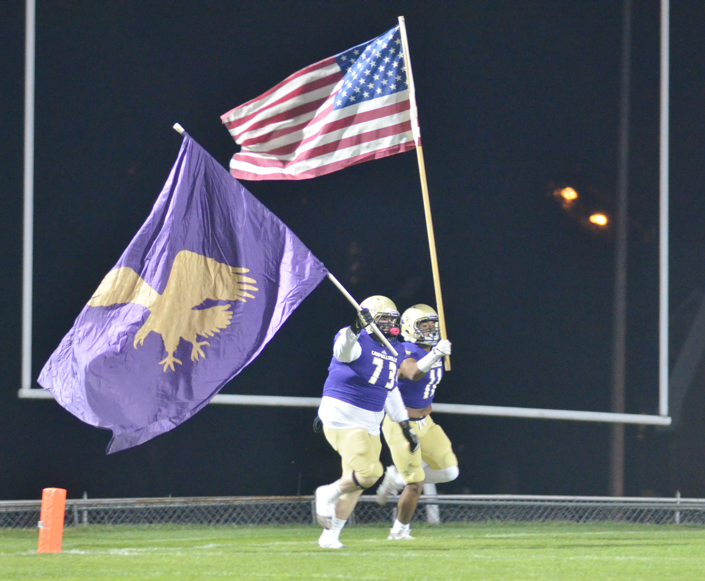 CHS senior Ryan Jeffries, at left, and sophomore Braden Paige run with the Eagle and American flags.