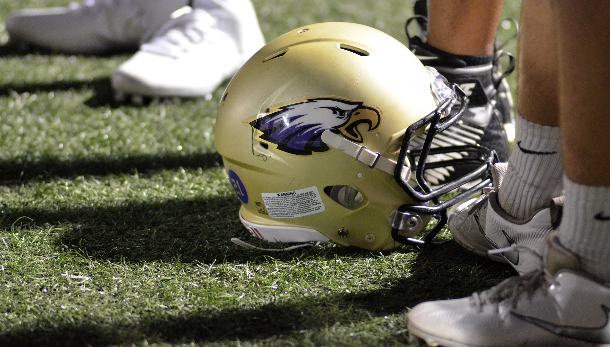 A CHS football helmet sits on the ground during a play.