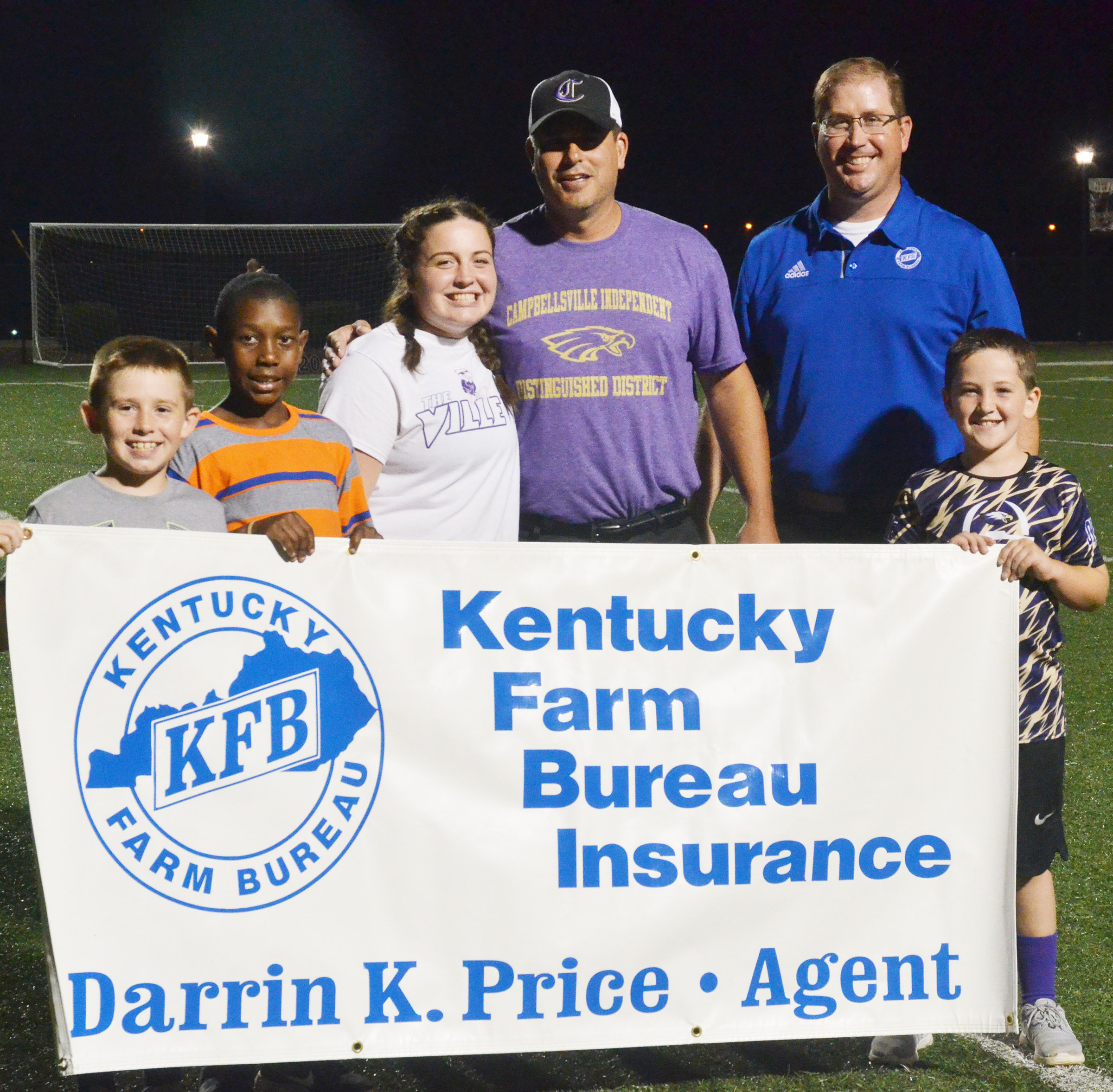 Kentucky Farm Bureau agent Darrin Price, in back, at right, sponsored a halftime field goal kick during the game. Campbellsville Independent Schools Superintendent Kirby Smith attempted the kick. If he made it, CHS senior Caitlin Bright took home $50. If not, she received $25. Despite his best effort, Smith missed the kick. From left are Campbellsville Elementary School third-graders Lanigan Price and Jaron Johnson, Bright, Smith, Price and third-grader Luke Adkins.