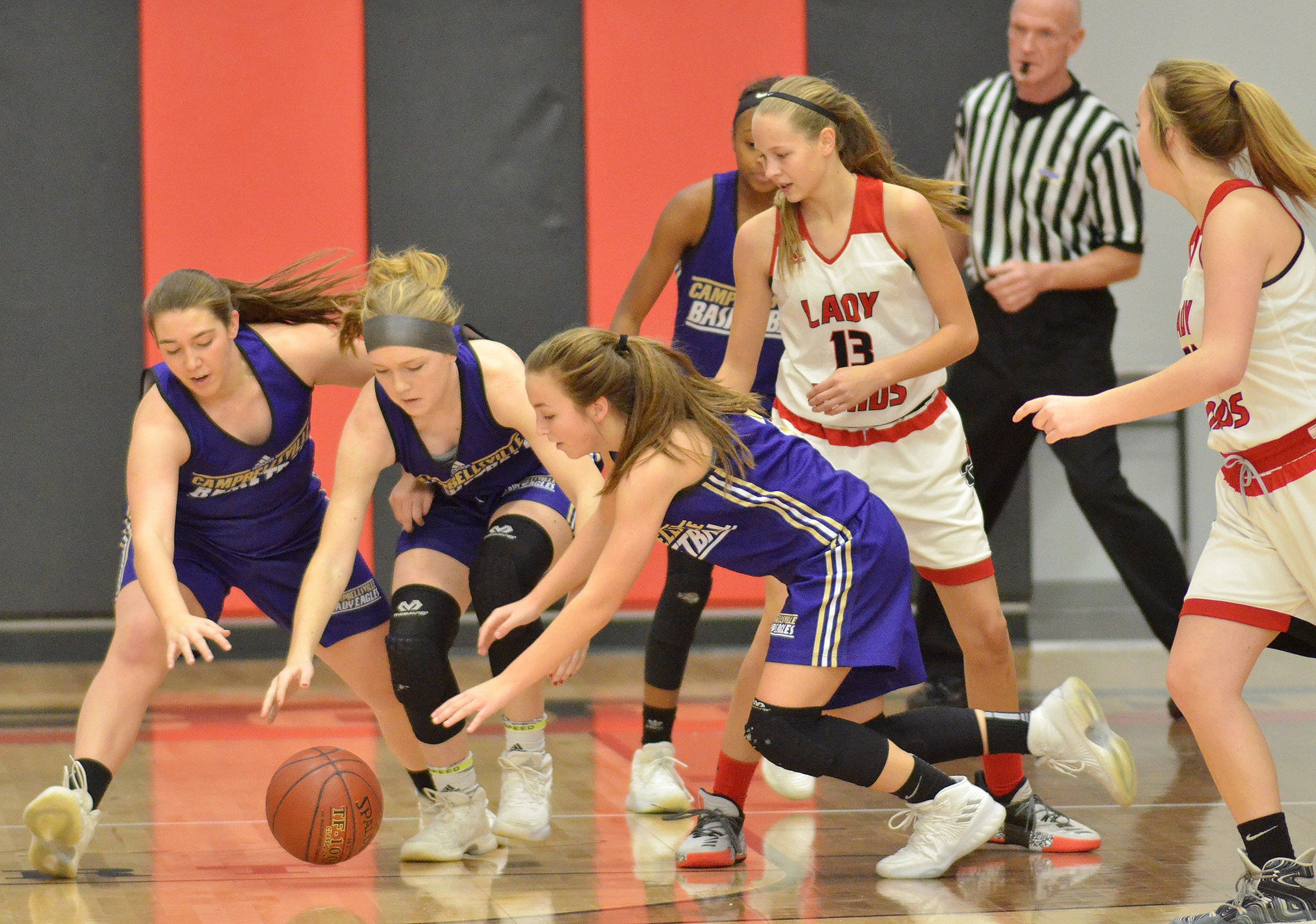 From left, CHS freshmen Abi Wiedewitsch and Catlyn Clausen and Campbellsville Middle School eighth-grader Lainey Watson fight for the ball.