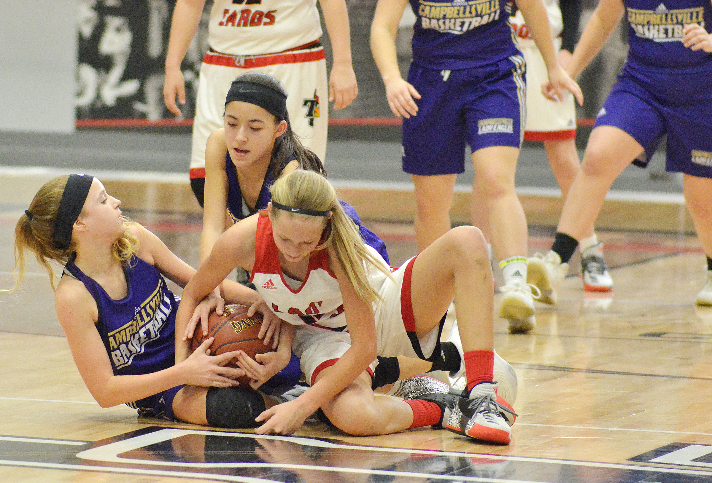 Campbellsville Middle School eighth-graders Rylee Petett, at left, and Kaylyn Smith fight for the ball.