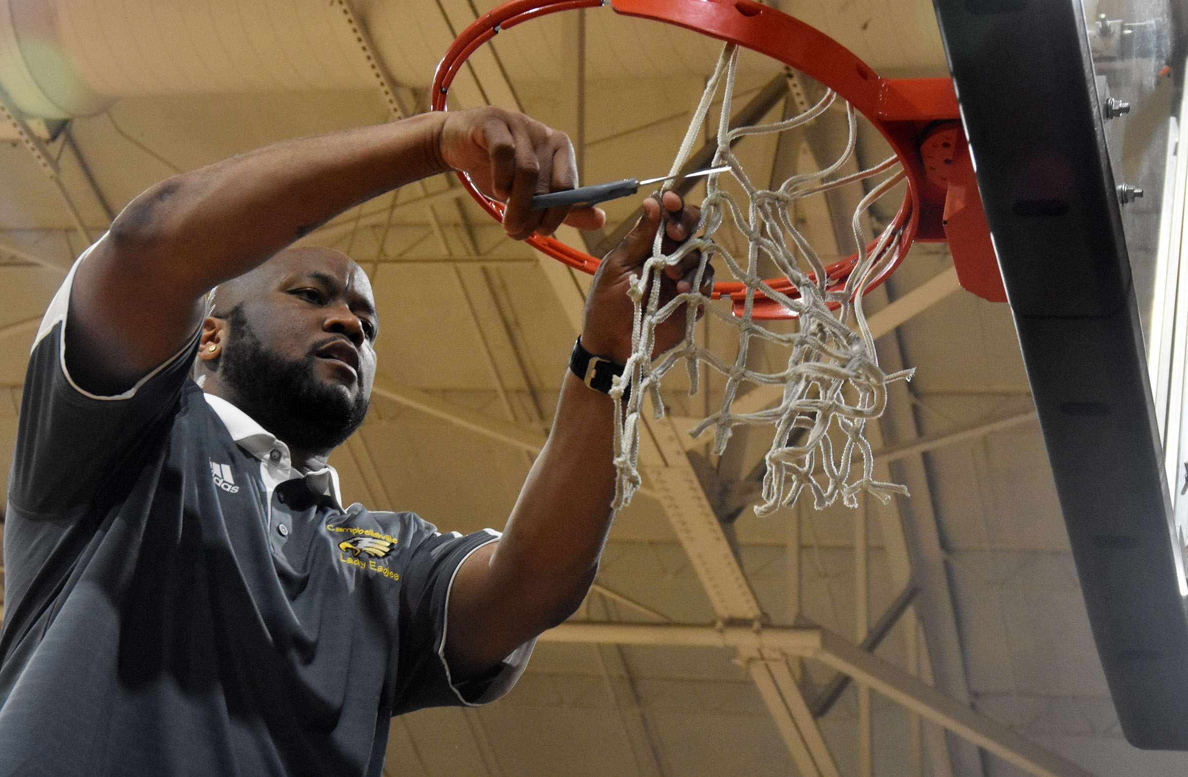 CHS girls' basketball head coach Anthony Epps cuts the net.