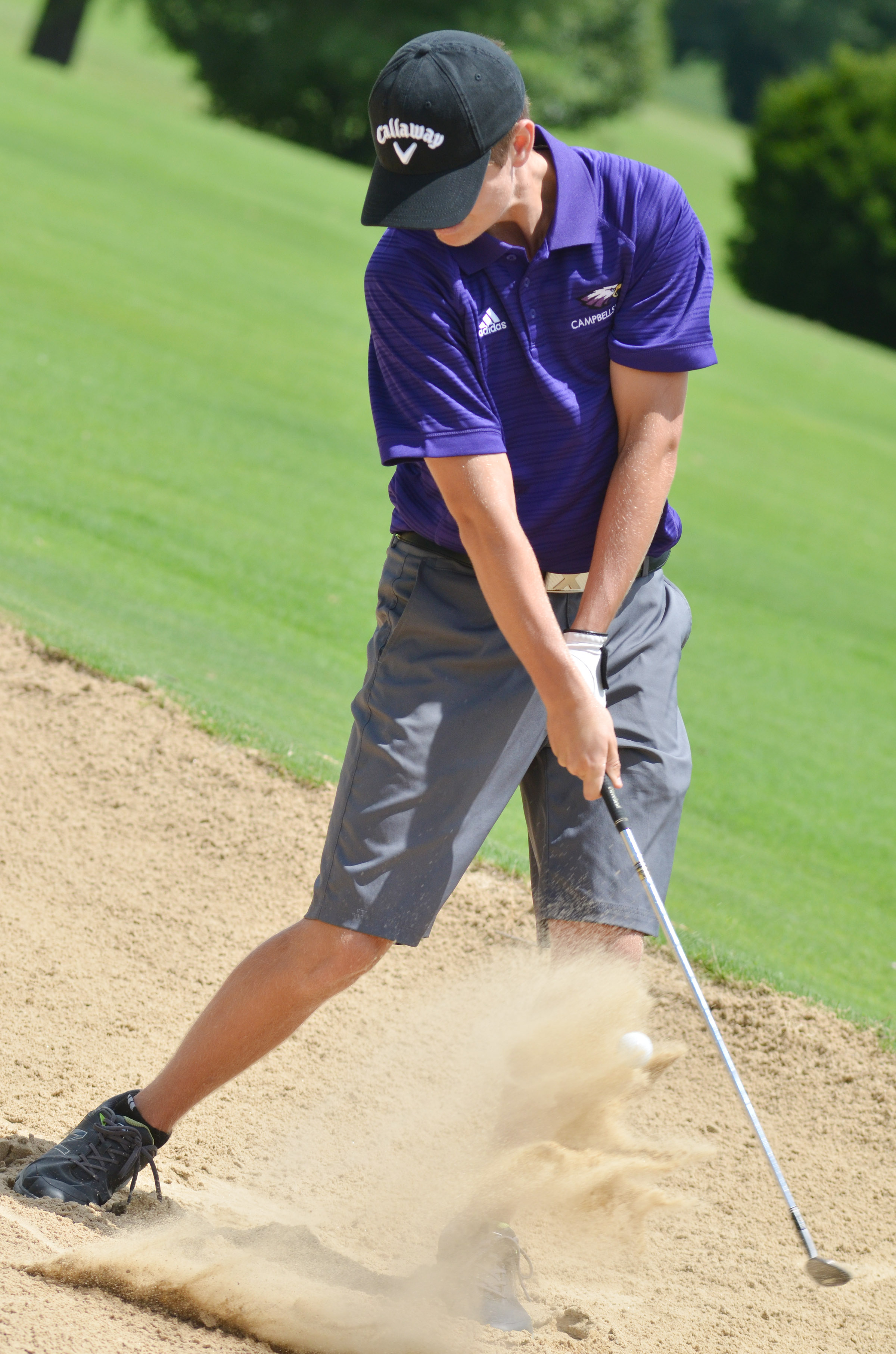 CHS junior Myles Murrell hits the ball out of a sand pit.