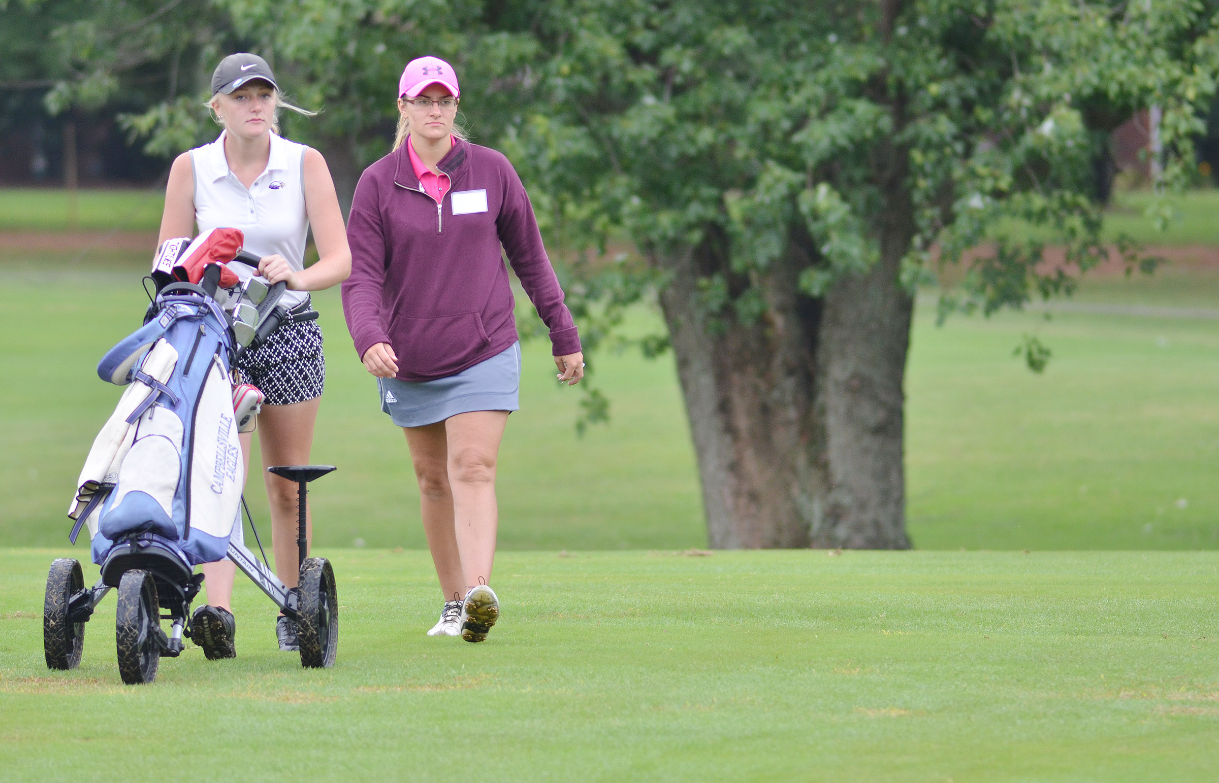 CHS junior Abbie Dicken walks to her ball with coach Ashley Goodin.