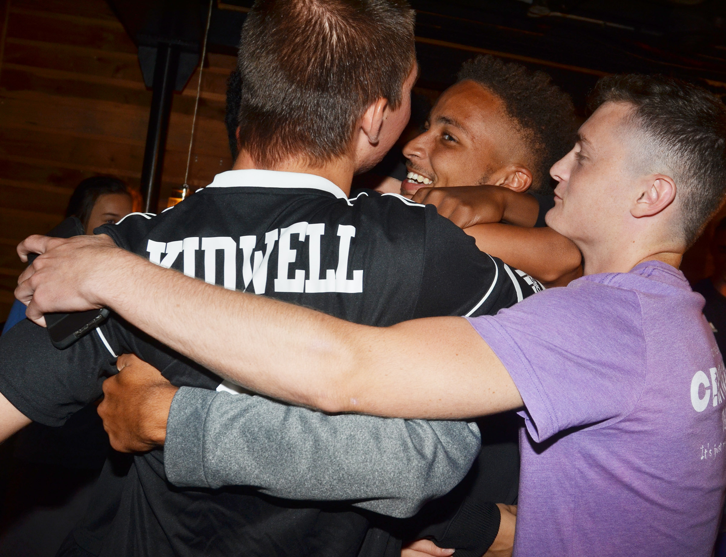 From left, CHS seniors Cass Kidwell, Ethan Lay and Bryce Richardson hug as the team celebrates at Creek Side Restaurant.