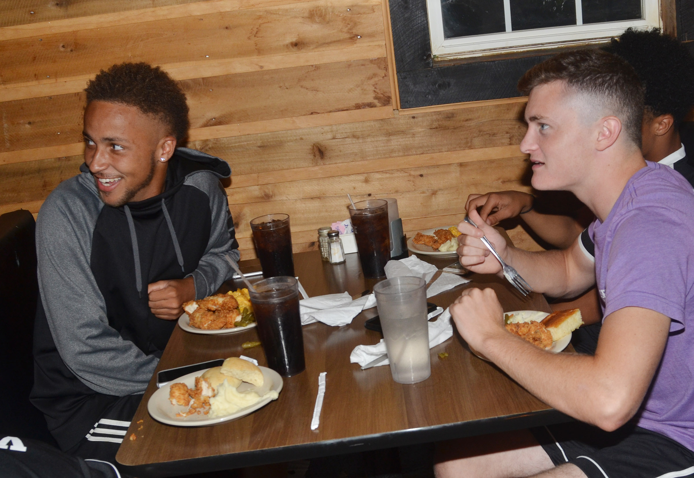 CHS seniors Ethan Lay, at left, and Bryce Richardson eat together as the team celebrates at Creek Side Restaurant.