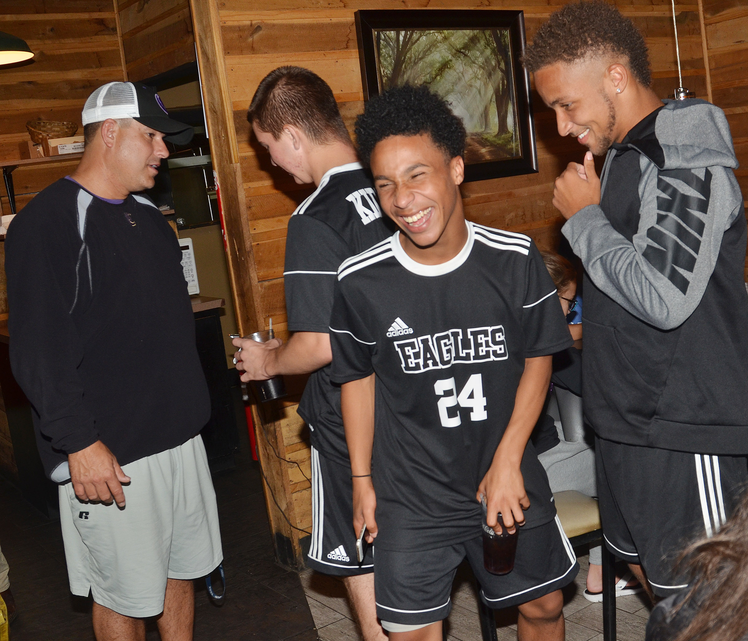 CHS junior Daniel Johnson, center, shares a laugh with senior Ethan Lay as the team celebrates at Creek Side Restaurant.
