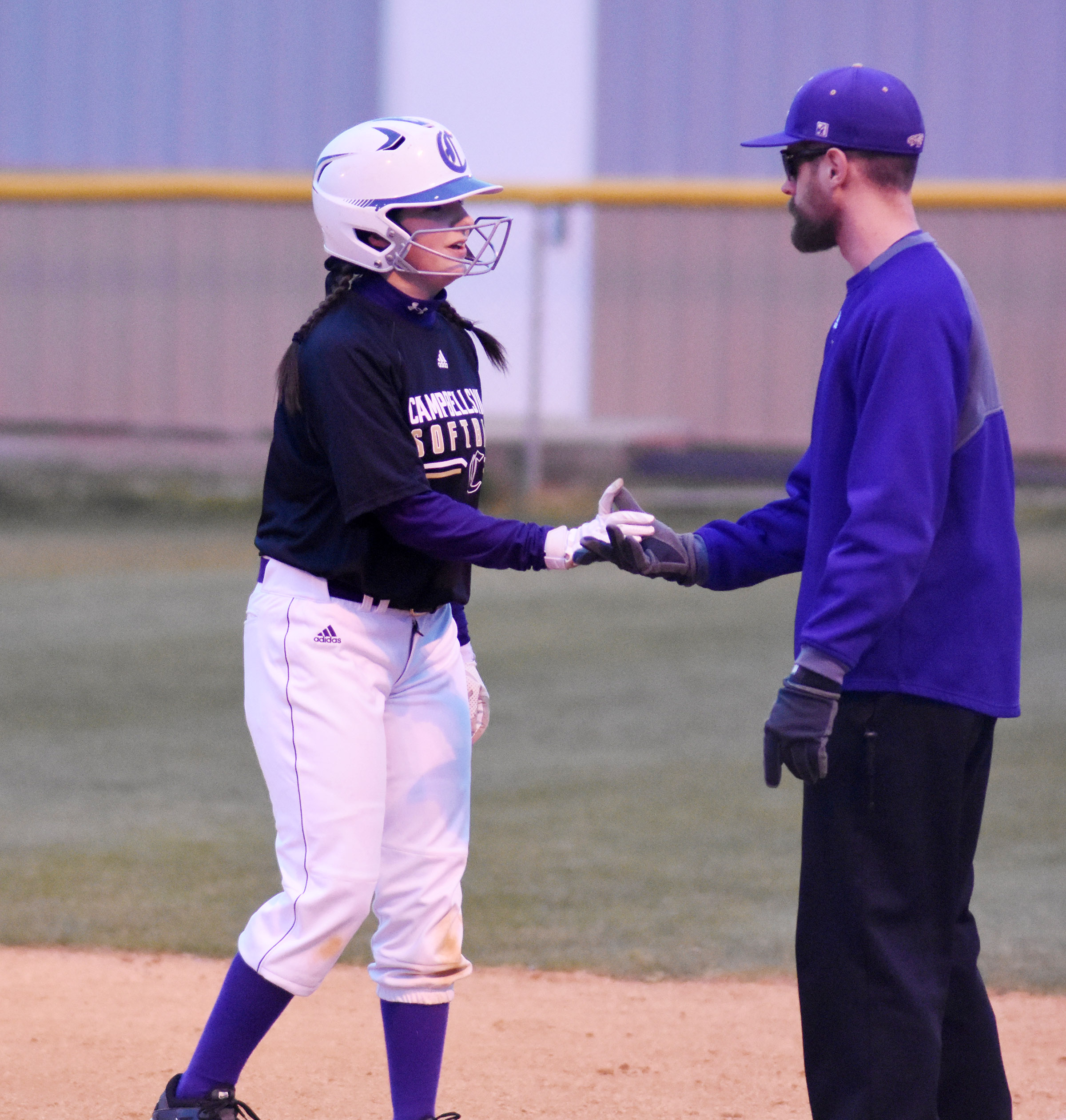CHS sophomore Sydney Wilson receives congratulations from assistant coach Matthew Schmuck after a base hit.