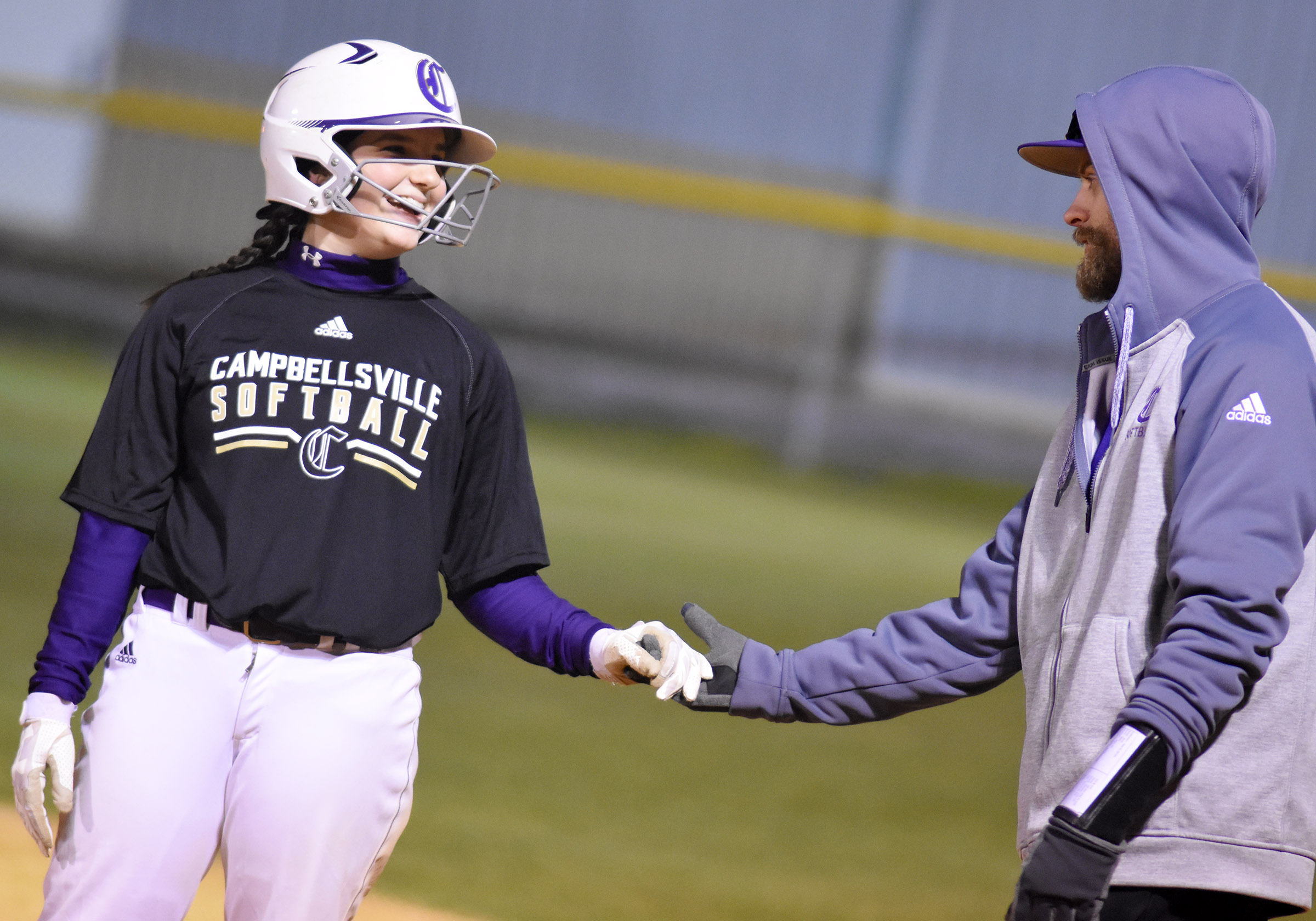 CHS sophomore Sydney Wilson is congratulated by assistant coach Matthew Schmuck after a hit.