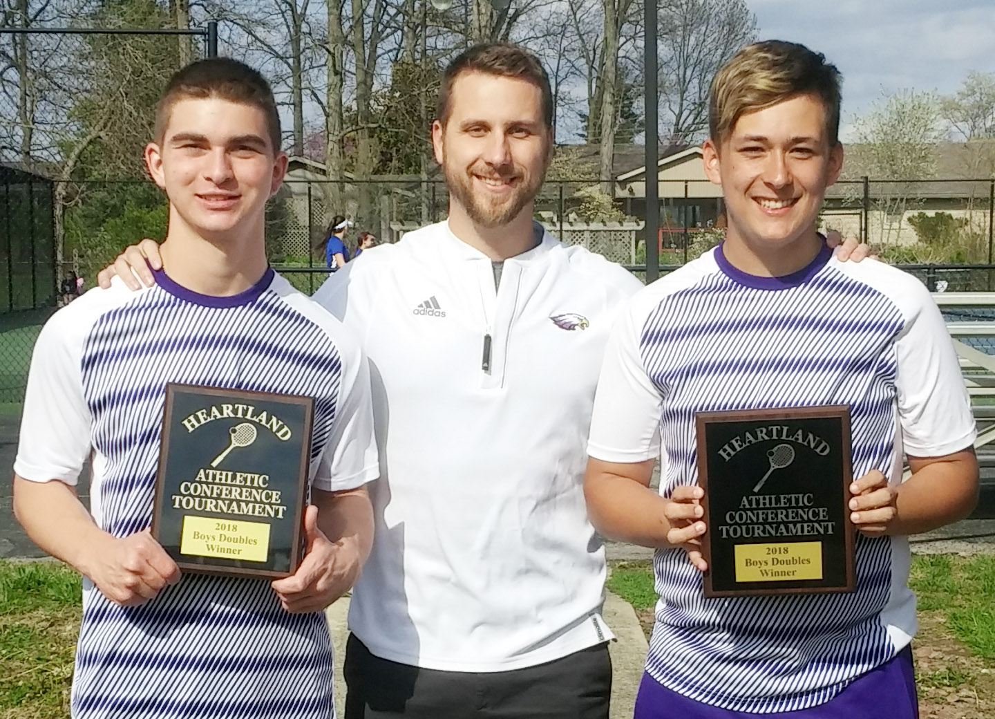 CHS boys' doubles team, senior Cass Kidwell, at left, and his classmate Cody Davis won three rounds to take home the Heartland Conference tennis tournament championship. They are pictured with their coach, Tyler Hardy.