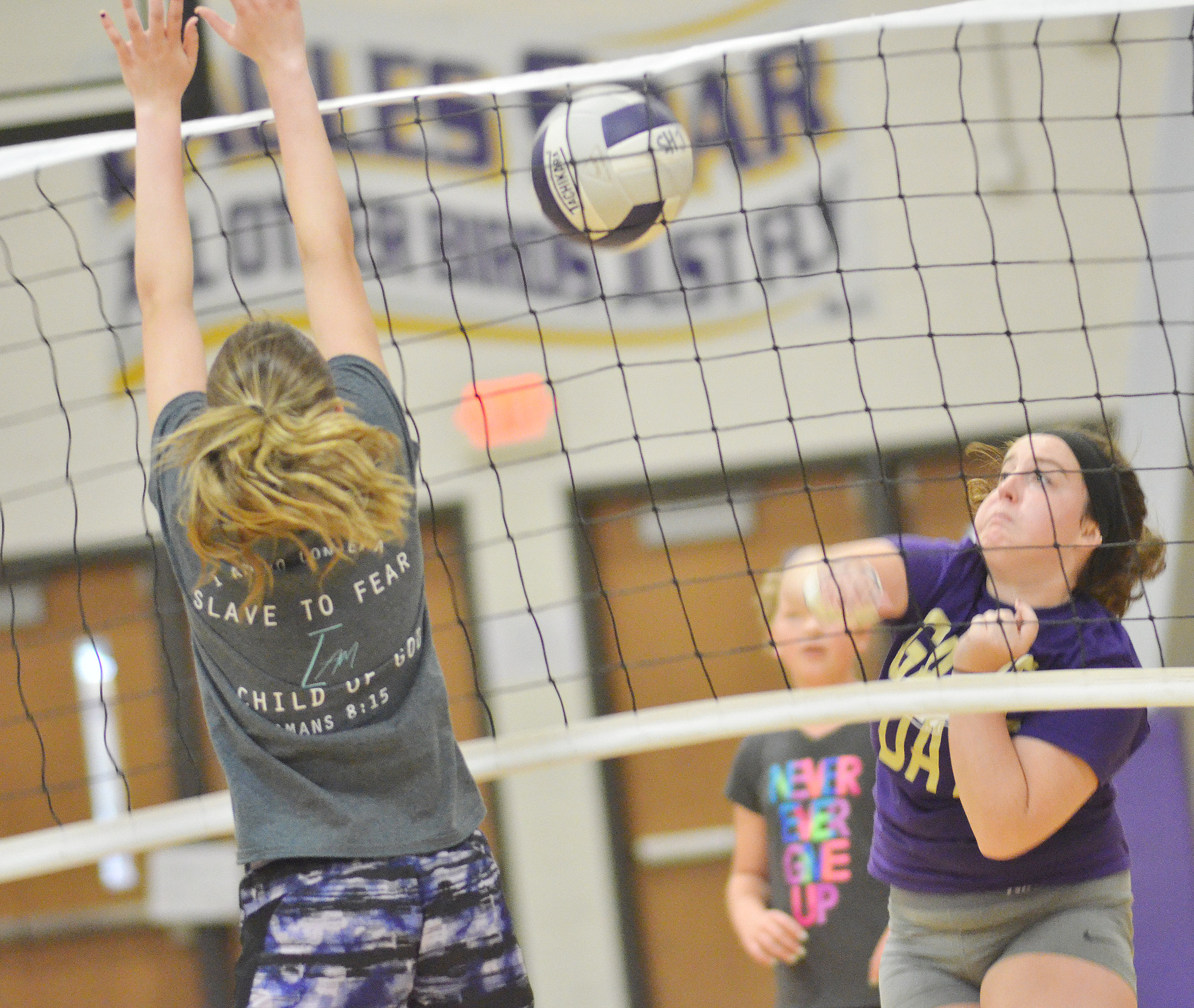 CHS senior Caitlin Bright hits the ball as freshman Zoie Sidebottom jumps to block it.