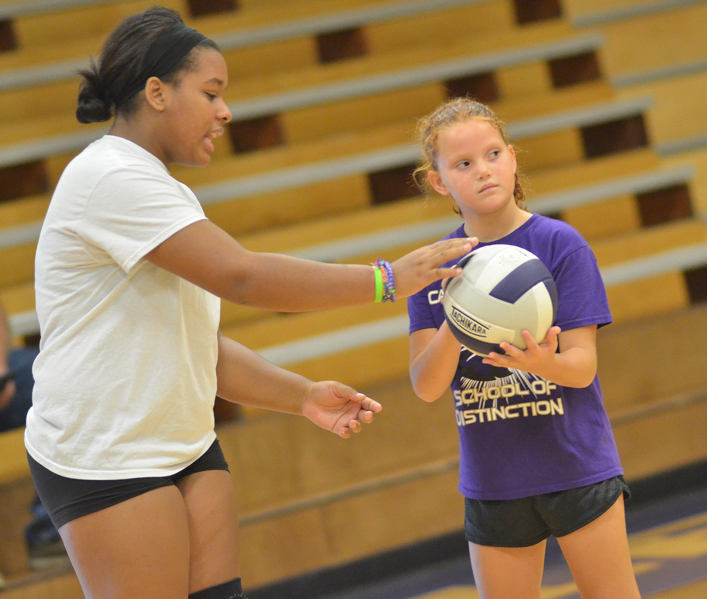 CHS senior Kayla Young helps CES third-grader Analeigh Foster position herself to serve.