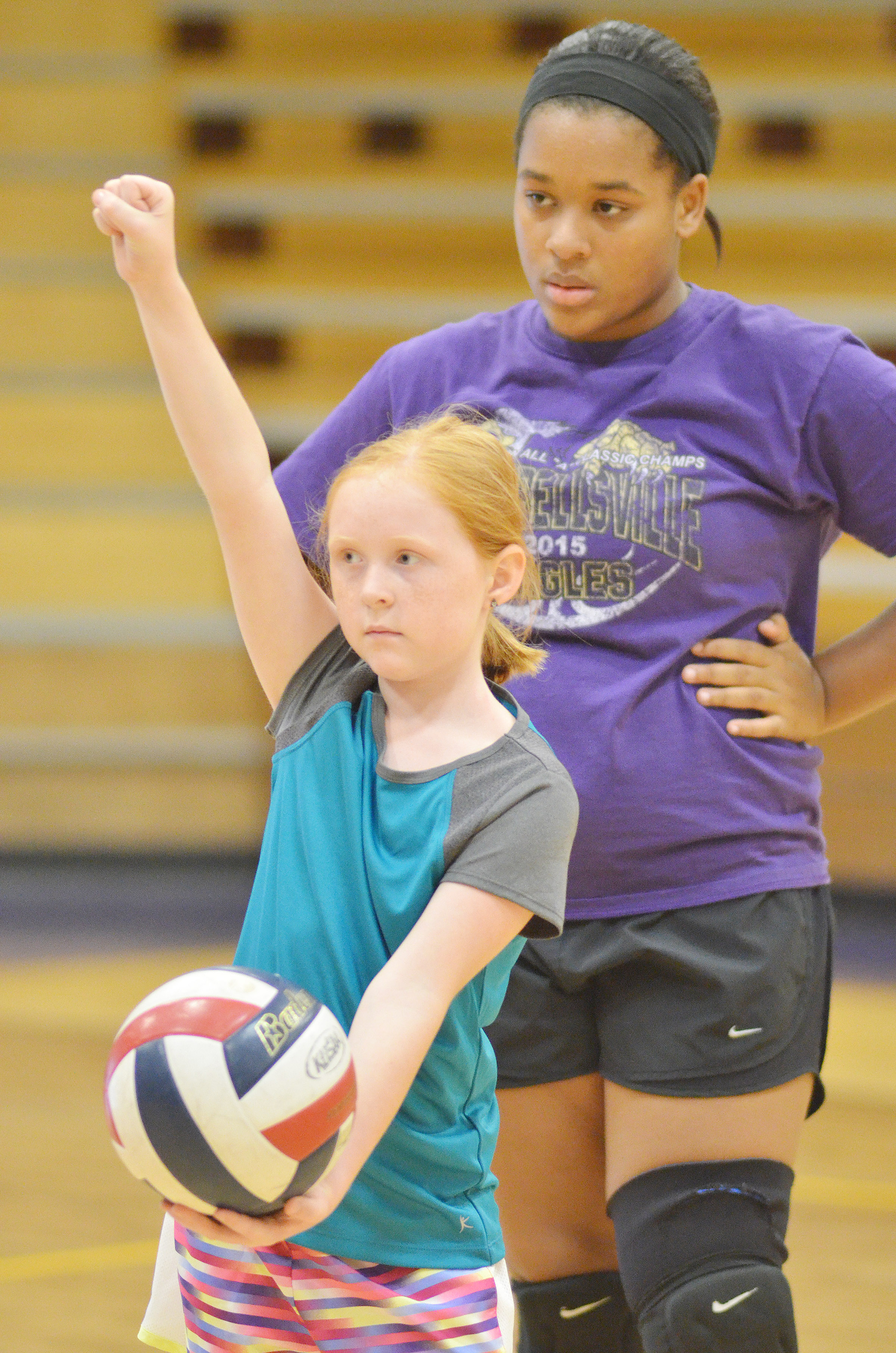 CHS senior Kayla Young watches as CES fourth-grader Nora Harris serves.