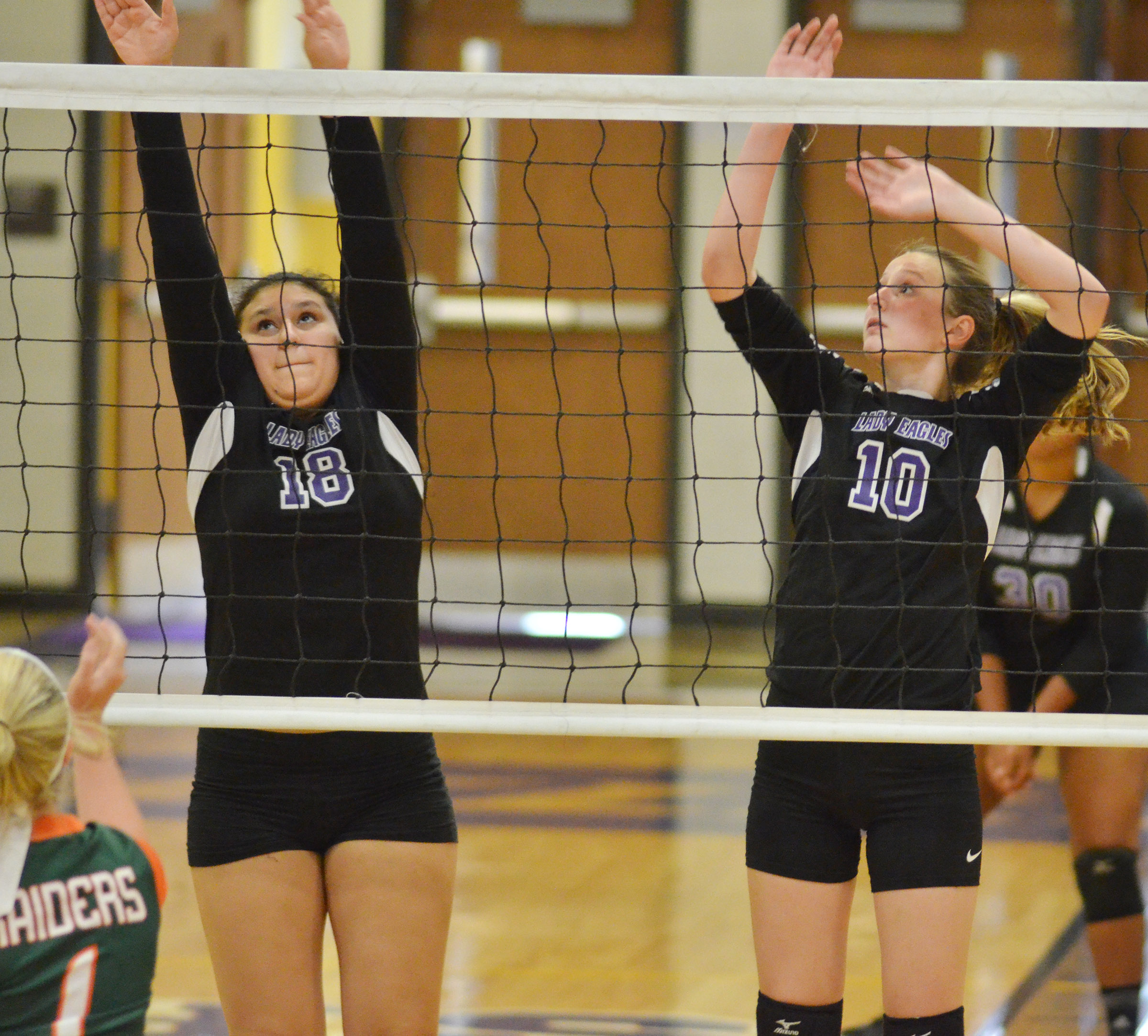 CHS freshmen Anna Clara Moura, at left, and Zoie Sidebottom jump to block the ball.