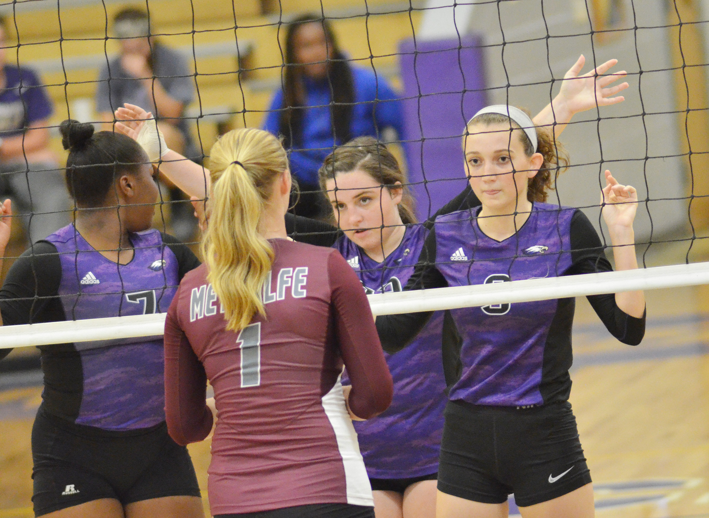 From left, CHS senior Kiyah Barnett and Caitlin Bright and junior Salena Ritchie get ready for the serve.