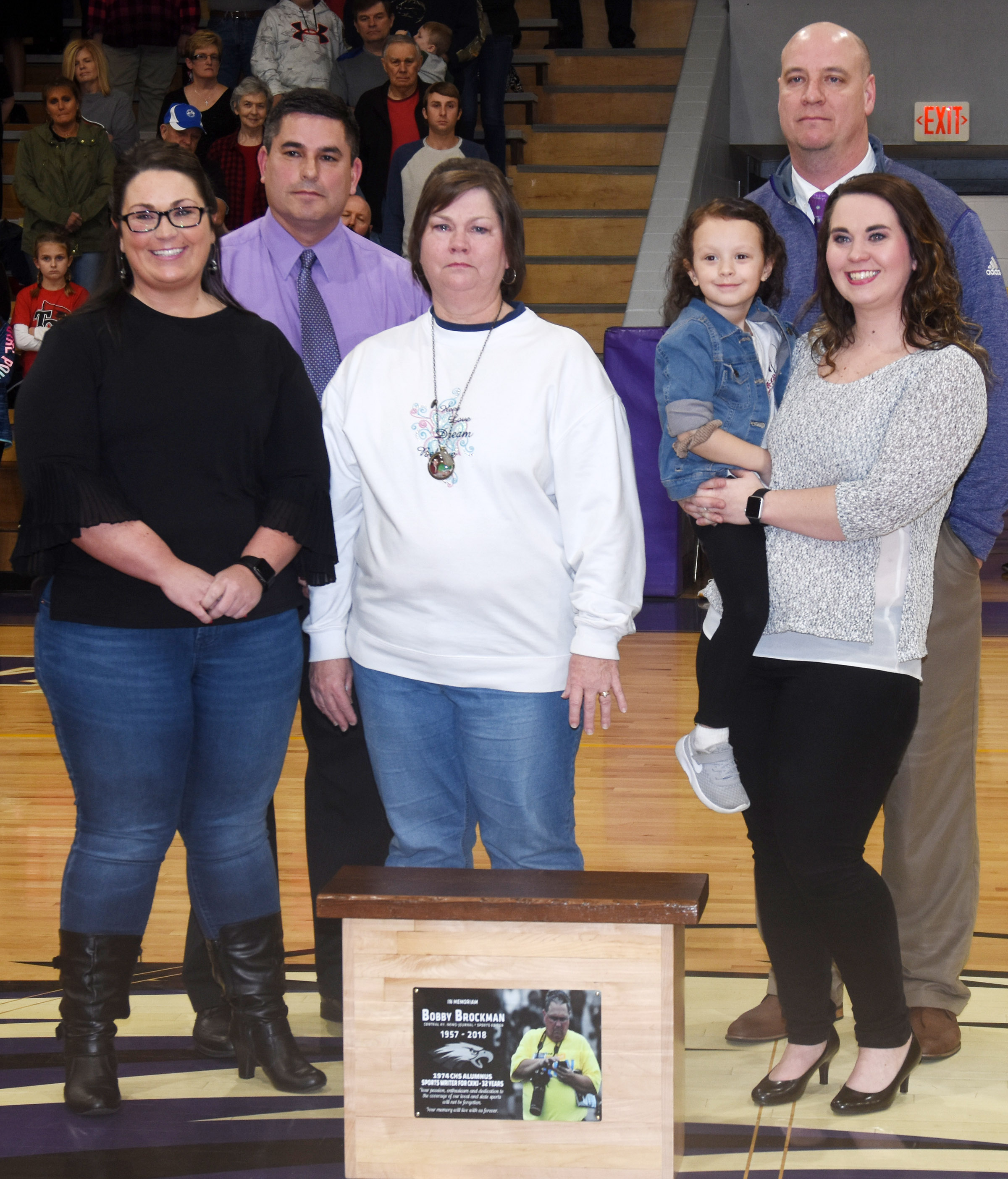 Bobby Brockman's family is presented a bench that was made out of his seat at the Campbellsville High School gymnasium. Pictured with CIS Superintendent Kirby Smith, in back, at left, and CHS Principal David Petett, are, from left, Brockman's daughter Rachel, his wife Sonja and his daughter Melanie holding his granddaughter Eden. Absent from the photo is Brockman's daughter Savanna, who is a sophomore at CHS.