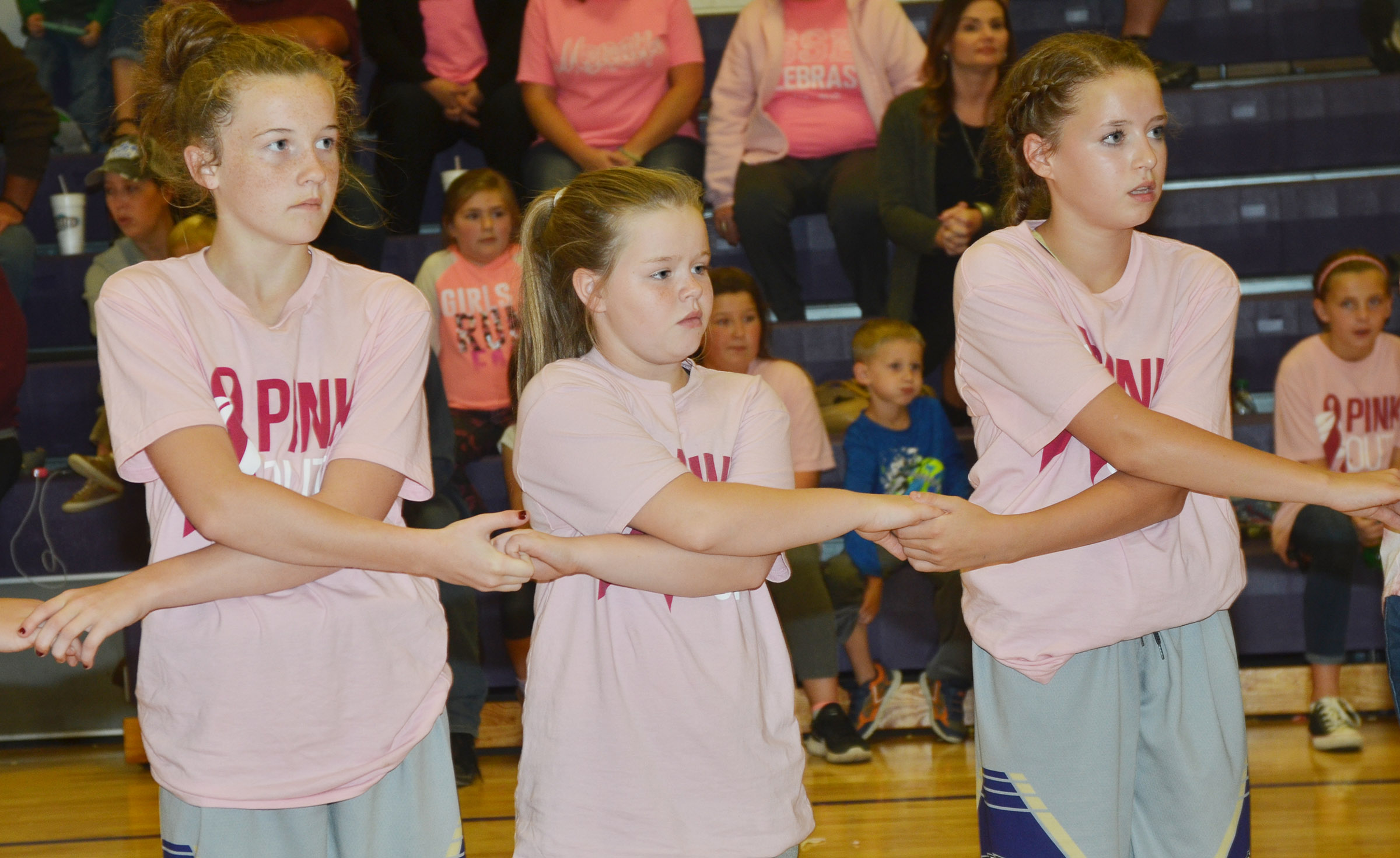 From left, CMS girls' basketball players Dakota Slone, a seventh-grader, fifth-grader Miley Hash and eighth-grader Rylee Petett pray with their teammates.