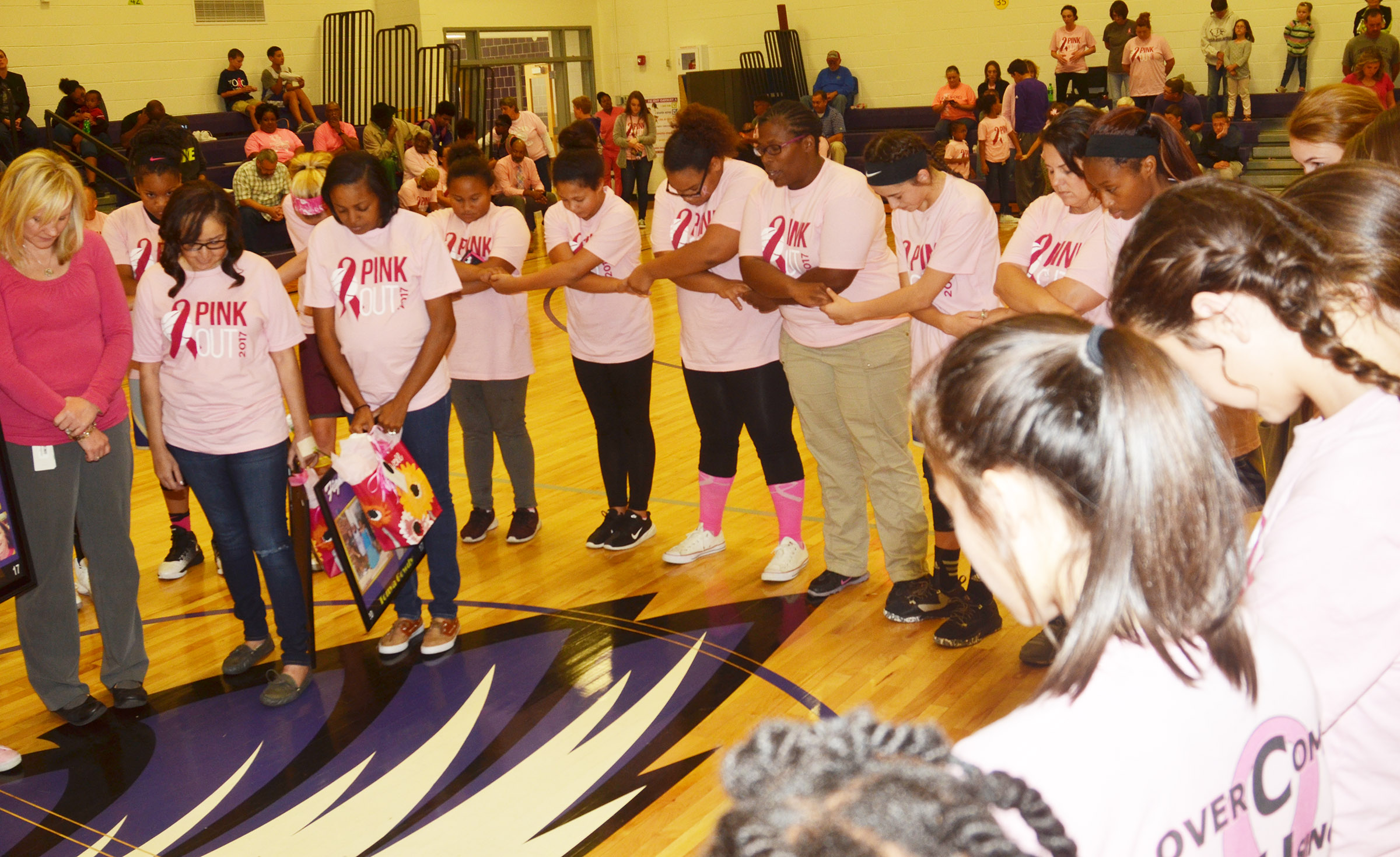 CMS girls' basketball players pray with the honored cancer survivors.