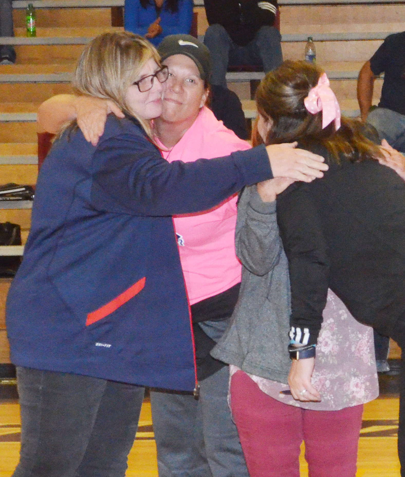 CHS head volleyball coach Elisha Rhodes hugs the cancer survivors honored on Thursday, Oct. 12.