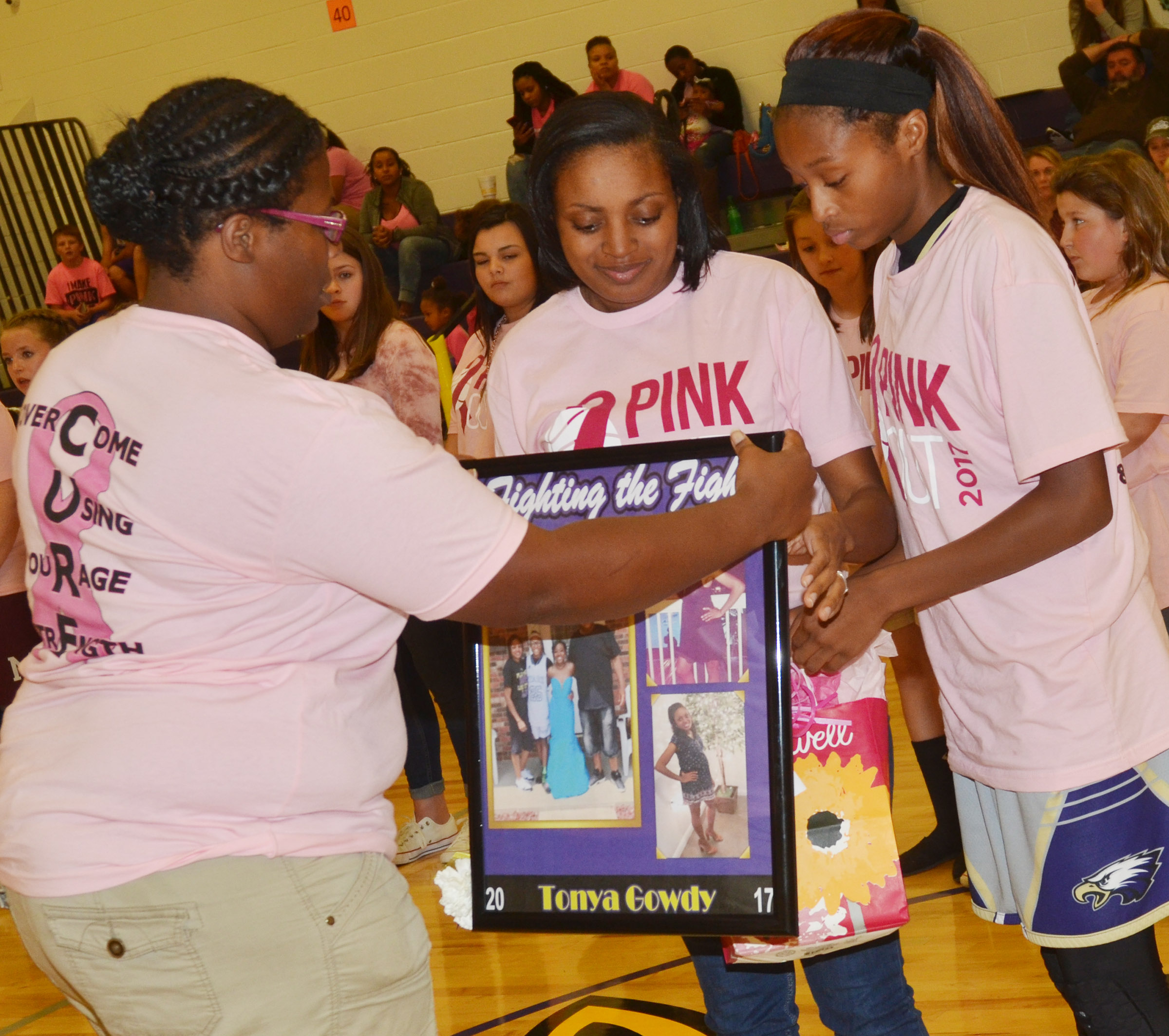 CMS girls' basketball head coach Tiarra Cecil honors Tonya Gowdy, who is eighth-grader Bri Gowdy's mother.