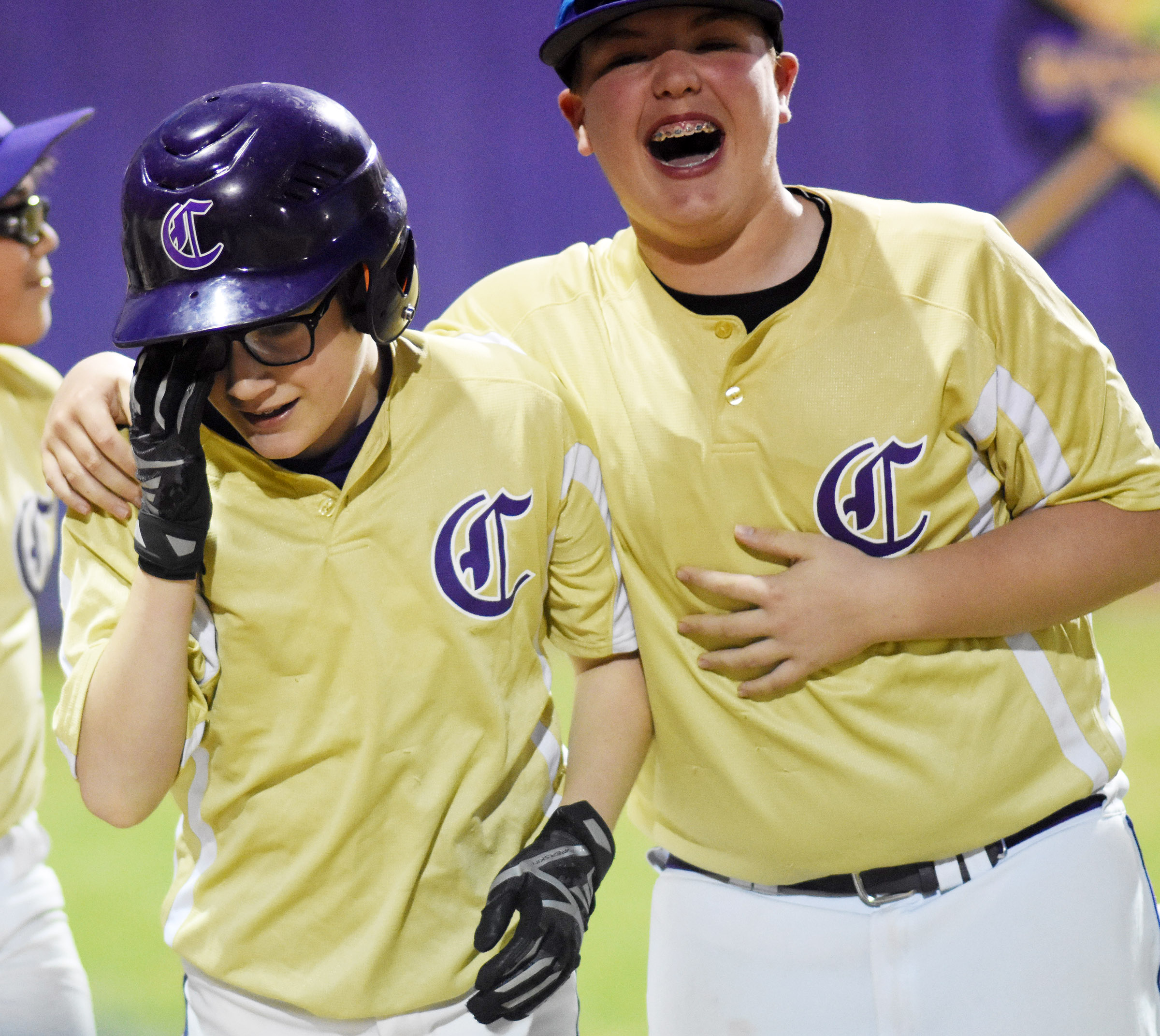 CMS seventh-grader Brady Hoosier celebrates with teammate Ryan Grubbs, a sixth-grader, after hitting an inside-the-park home run.