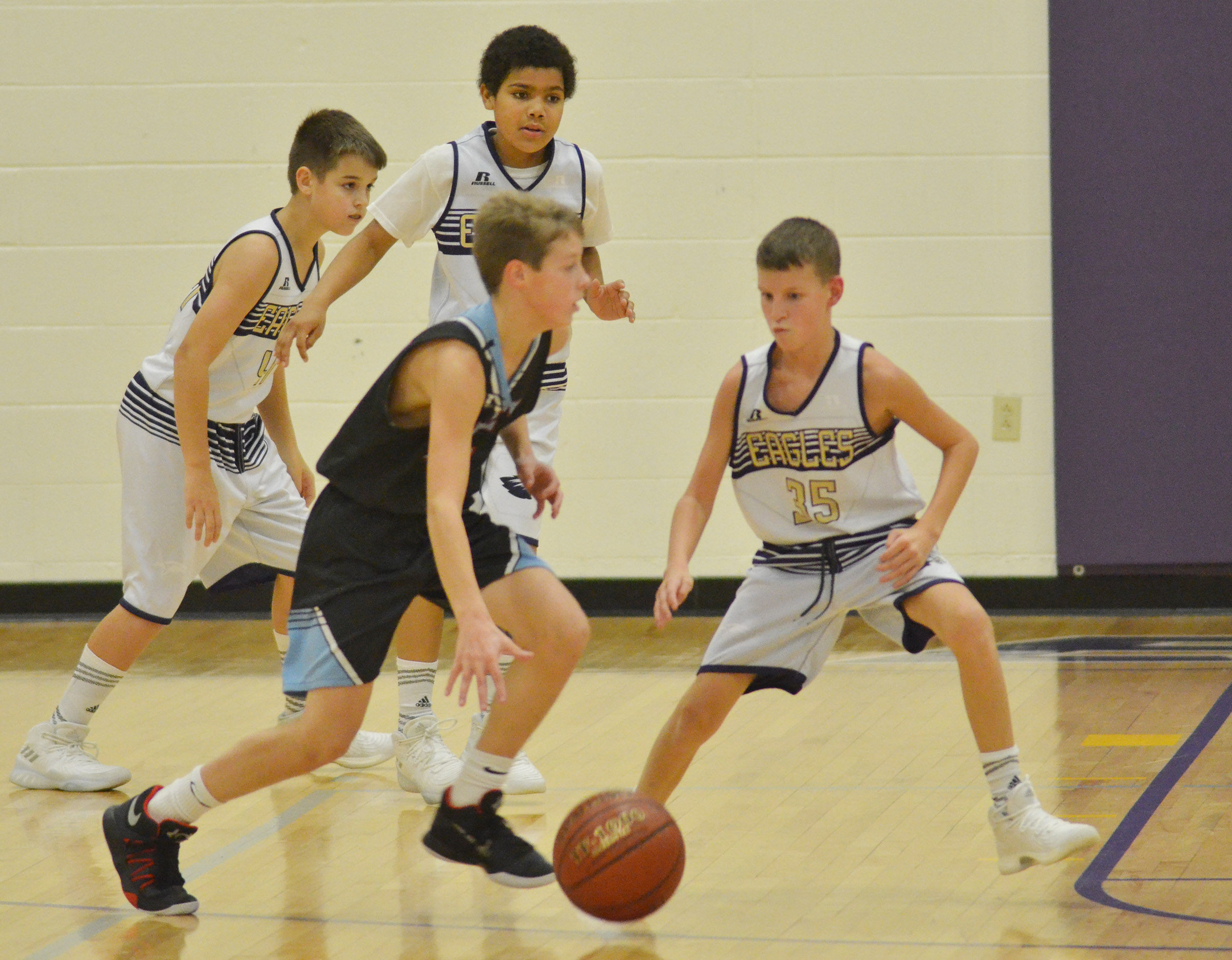 CMS sixth-graders Kaden Bloyd and Tashaun Hart, at left, and Campbellsville Elementary School fifth-grader Rowan Petett play defense.