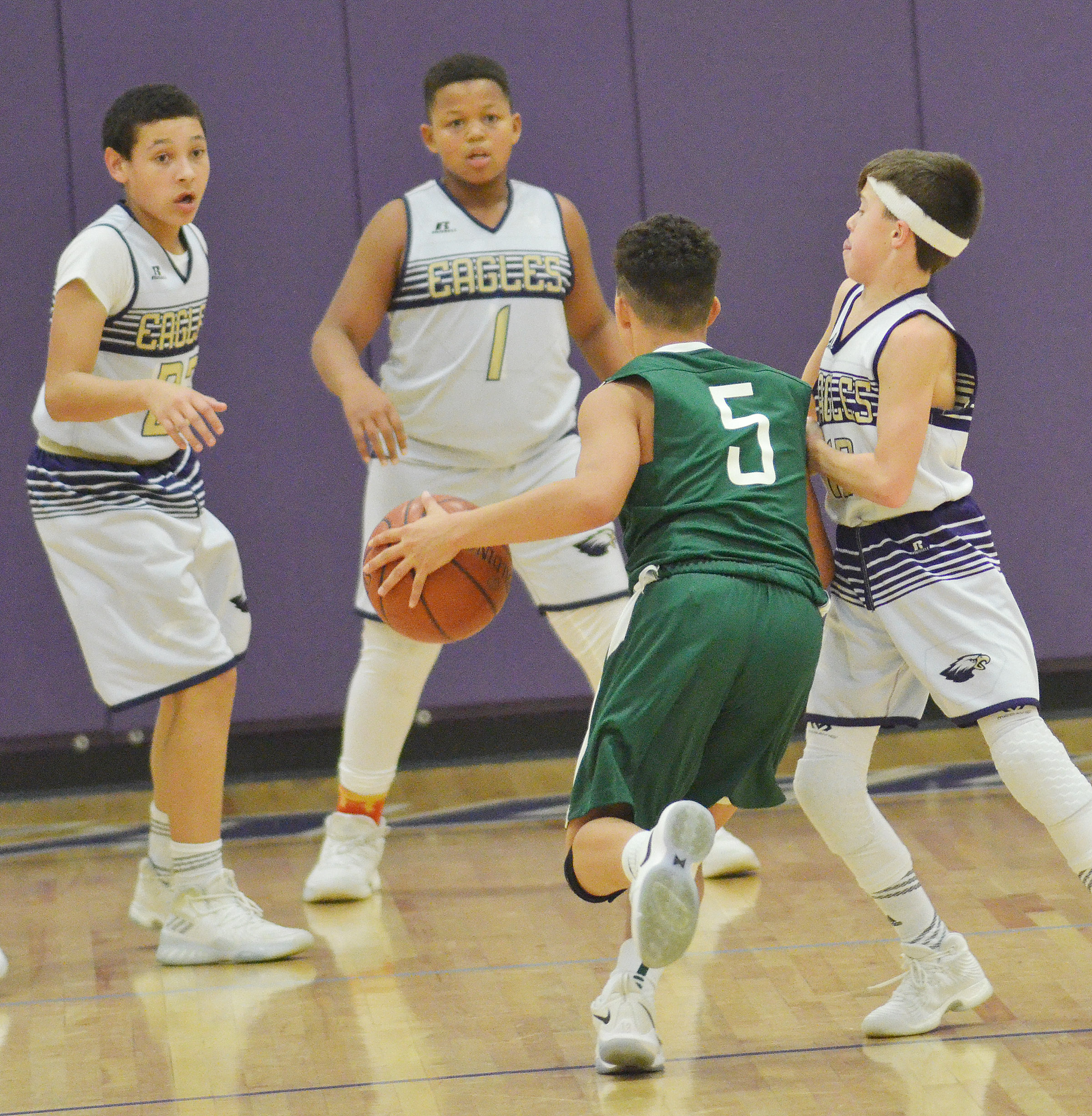From left, CMS eighth-grader Brice Spaw and seventh-graders Keondre Weathers and Chase Hord play defense.