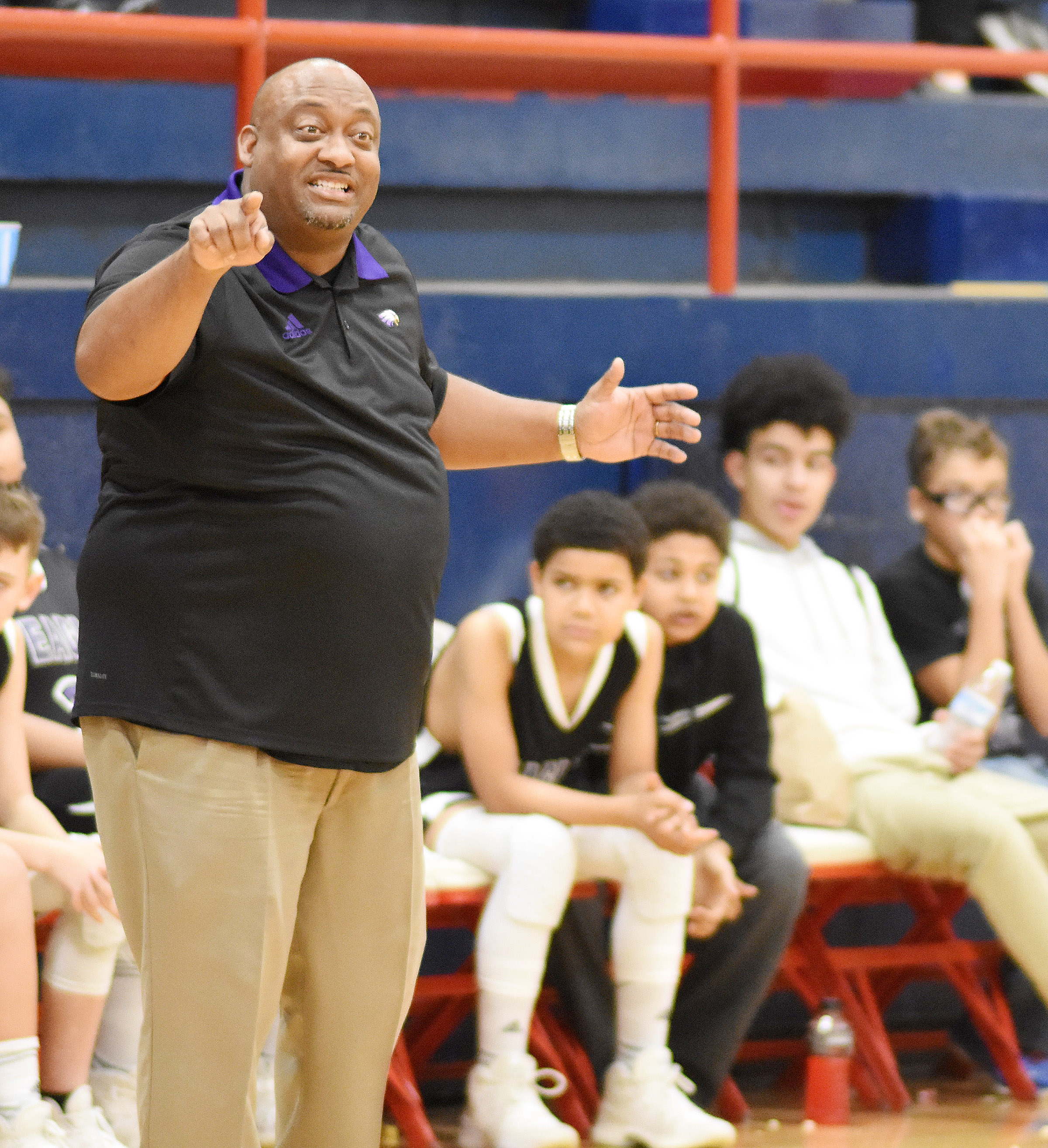 CMS boys' basketball coach Joseph Taylor talks to his players.