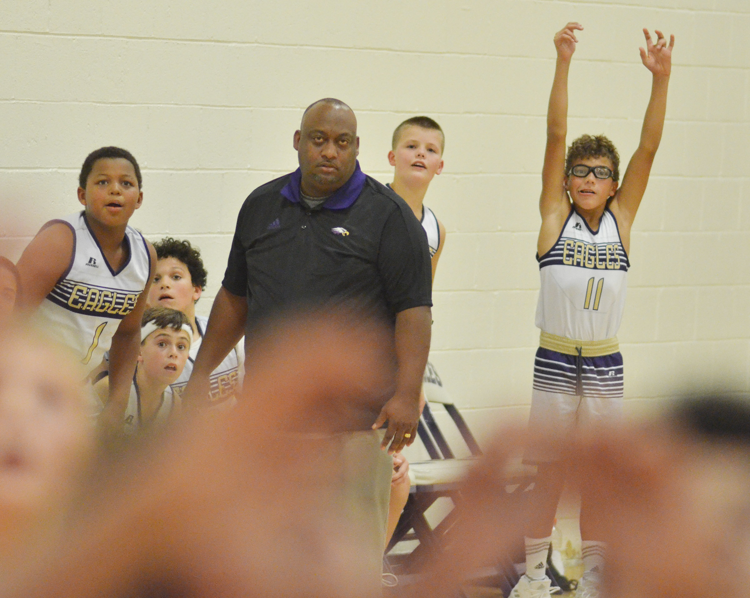 CMS boys' basketball head coach Joseph Taylor and his players watch a play.