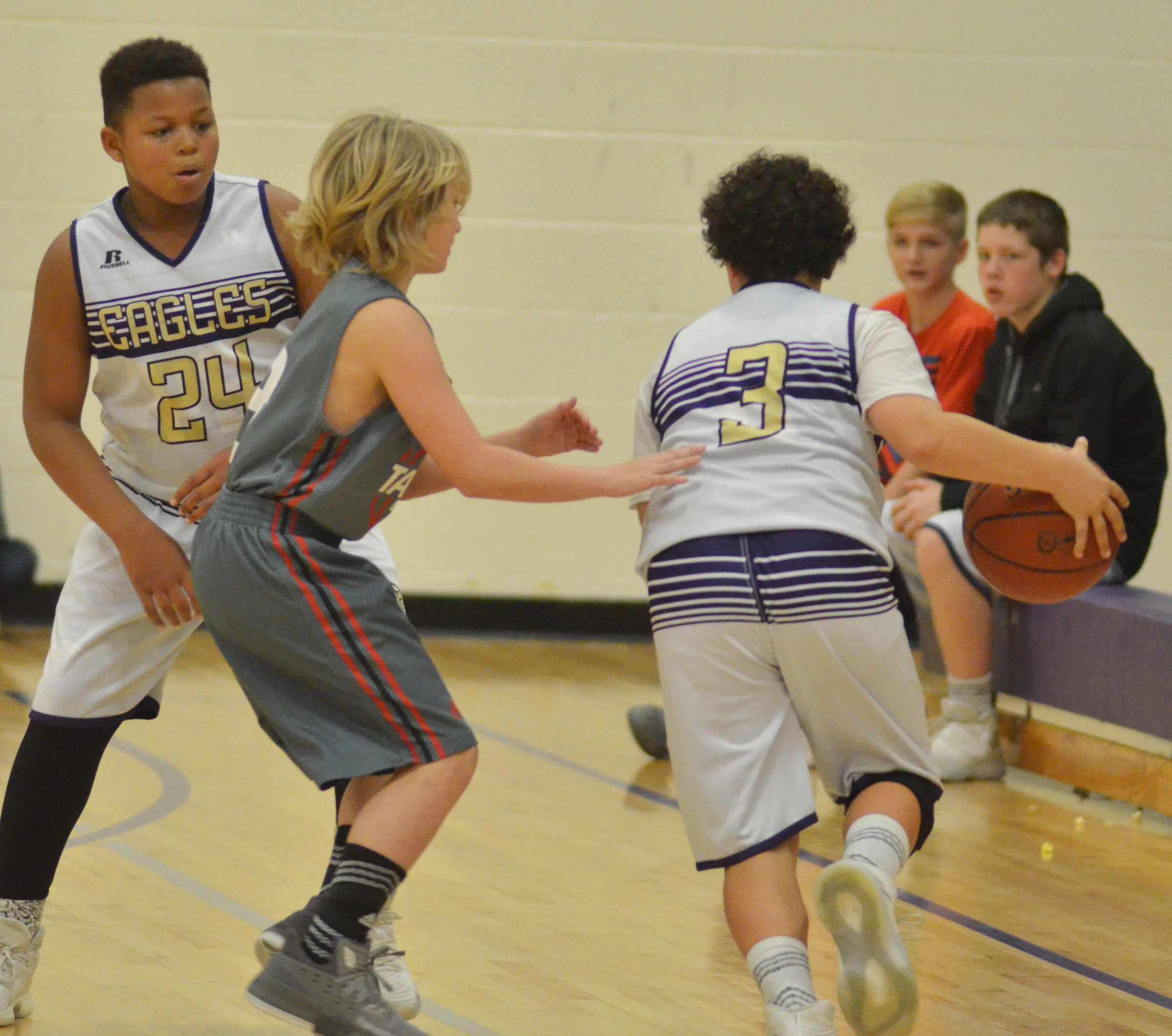 CMS seventh-grader Kaydon Taylor drives the ball as classmate Keondre Weathers plays defense.