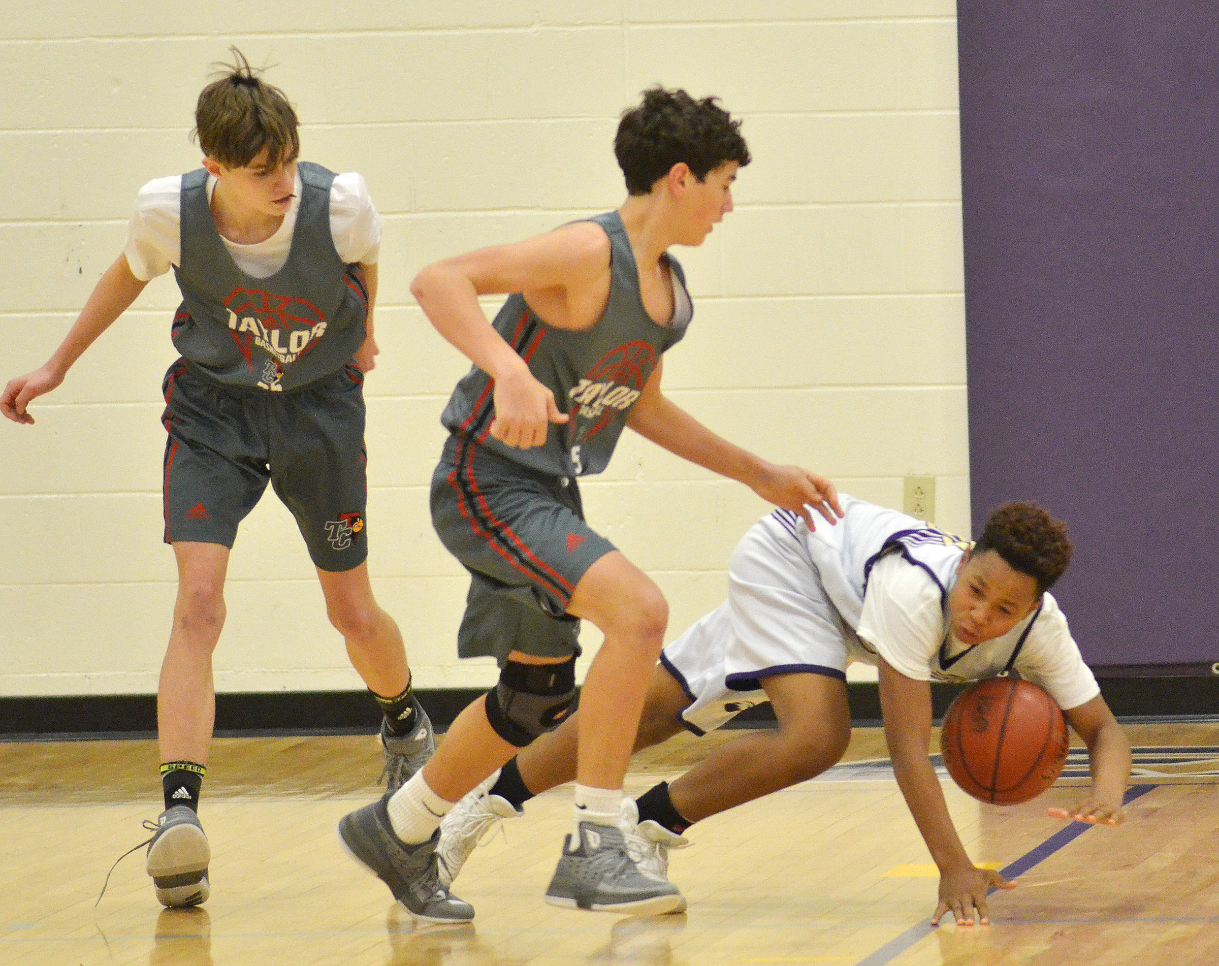 CMS seventh-grader Deondre Weathers lands on the floor as he protects the ball.