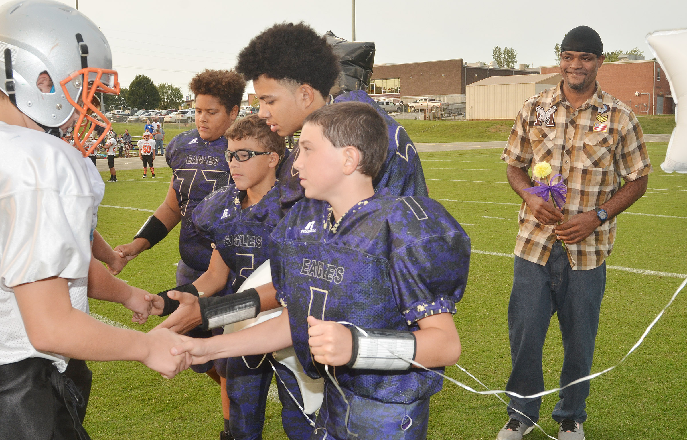 CMS eighth-graders, from left, Brandon Pittman, Logan Phillips, Adrien Smith and Dakota Harris shake hands with Hart County players. At right is William Smith, the father of Adrien Smith and the late Cameron Smith.