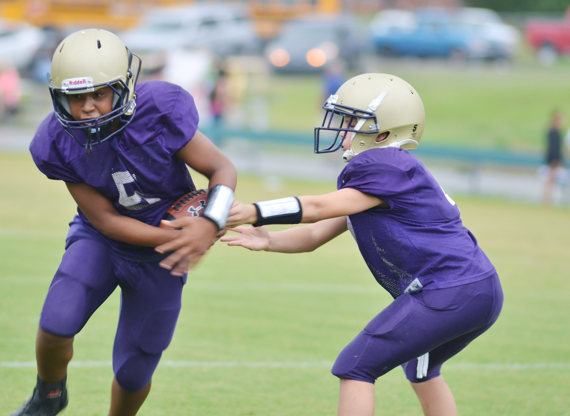 CMS seventh-grader Konner Forbis hands the ball to classmate Deondre Weathers.