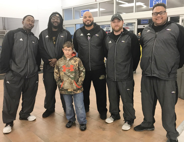 Campbellsville Elementary School fourth-grader Stanley Napper, in front, shops with CMS football coaches, from left, John Gholston, Shumari Bridgewater, Aaron Webb, Isaiah Perkins and Bronson Gowdy. Absent from the photo is coach Will Griffin.