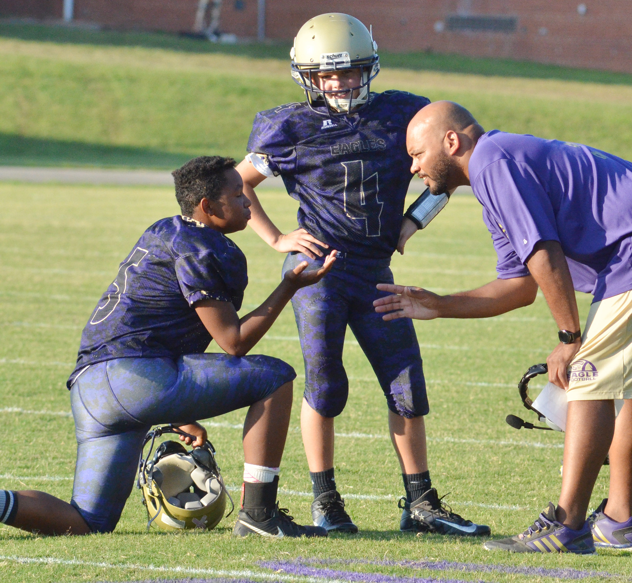 CMS seventh-graders Deondre Weathers, at left, and Konner Forbis talk to head coach Aaron Webb during a time out.