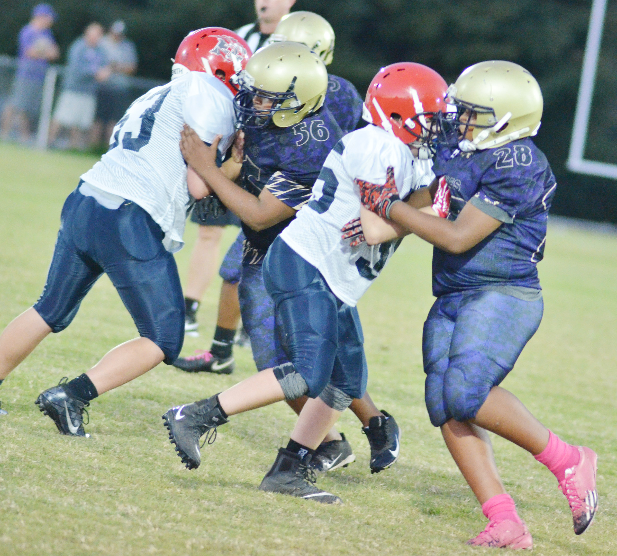 CMS seventh-grader Keondre Weathers, at right, and his teammates tackle.