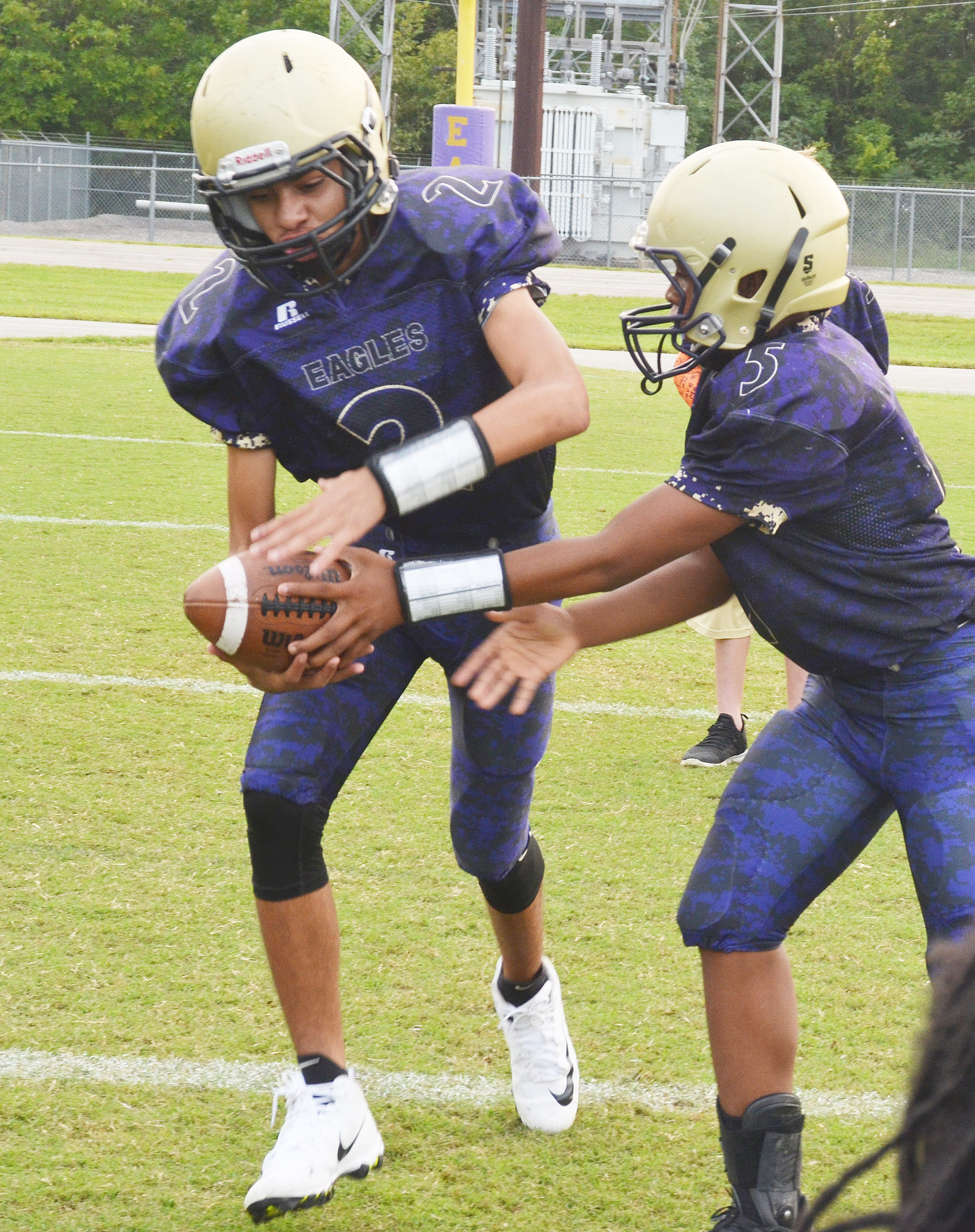 CMS seventh-grader Deondre Weathers hands the ball to eighth-grader Adrien Smith.