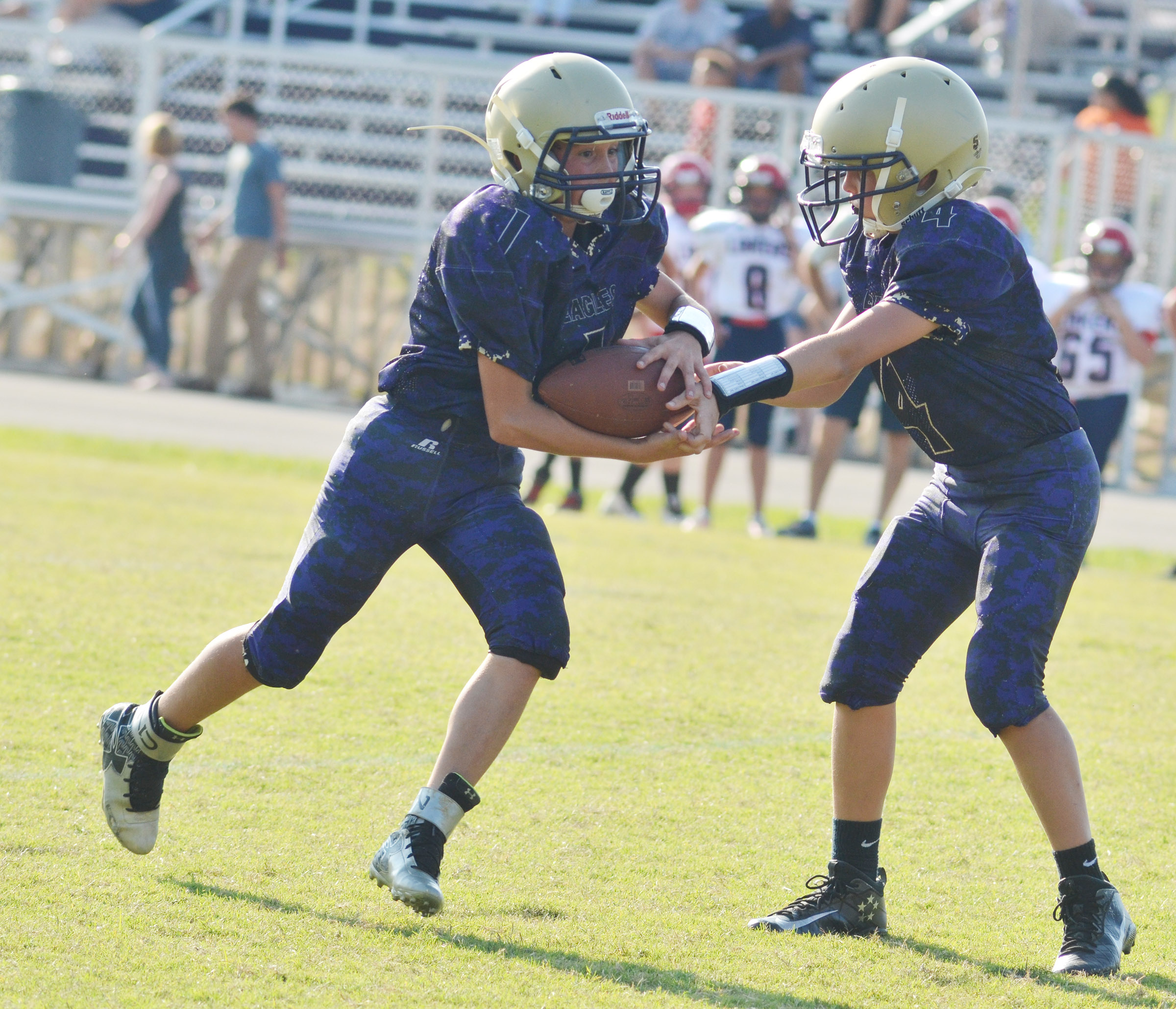 CMS seventh-grader Konner Forbis hands the ball to eighth-grader Dakota Harris.