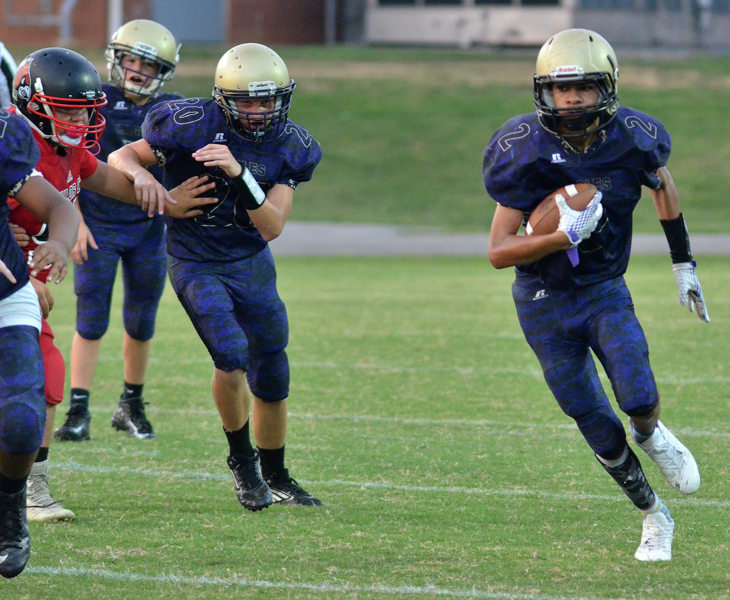 CMS eighth-grader Adrien Smith runs the ball, as seventh-grader Damon Johnson blocks for him.