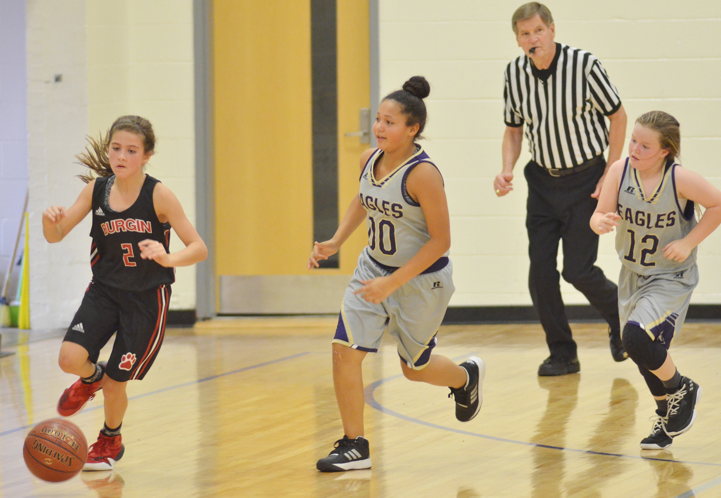 Campbellsville Elementary School fifth-graders Kenya Bridgewater, center, and Miley Hash, at right, run down the court.