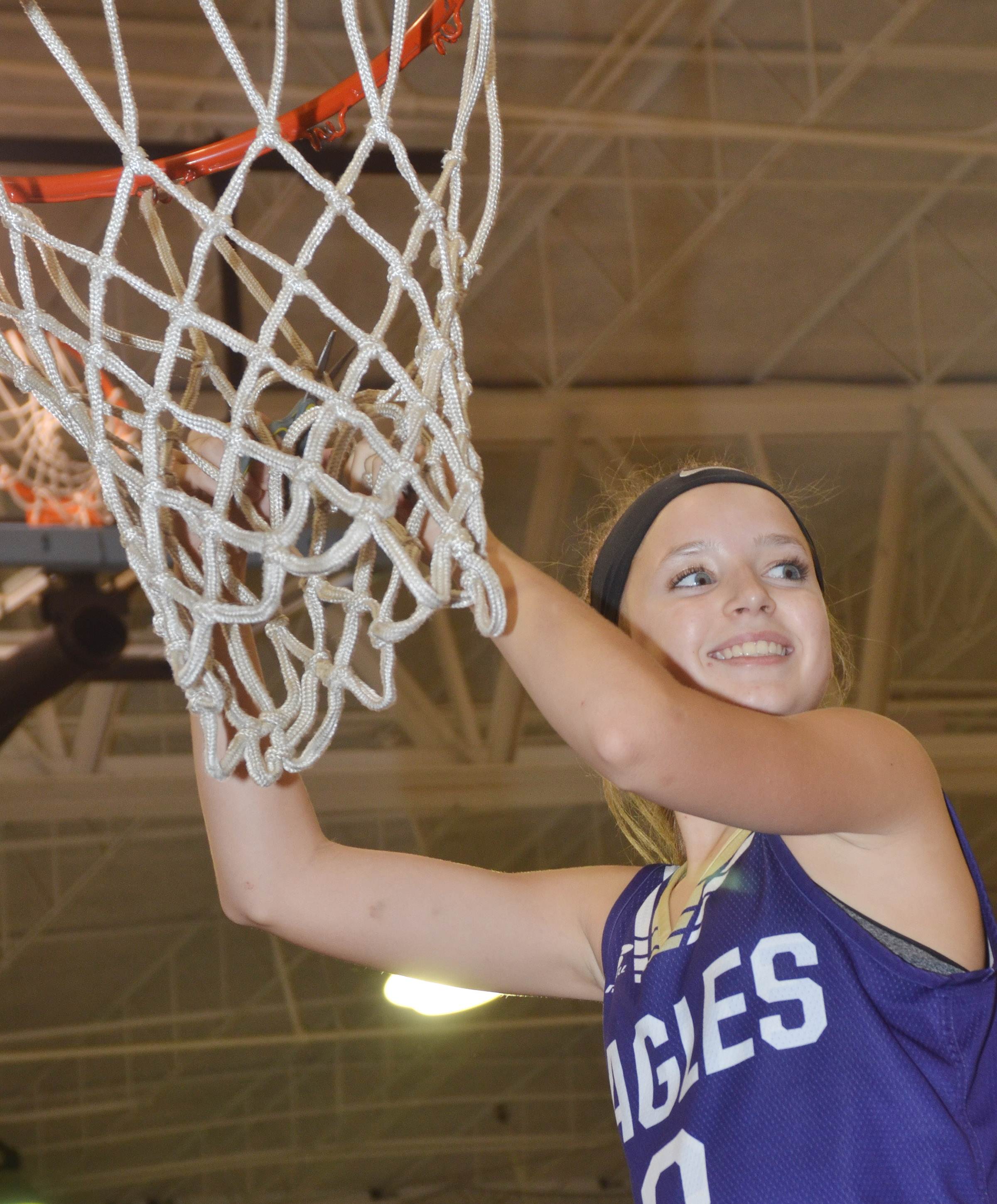 CMS eighth-grader Rylee Petett smiles as she cuts down the championship net.
