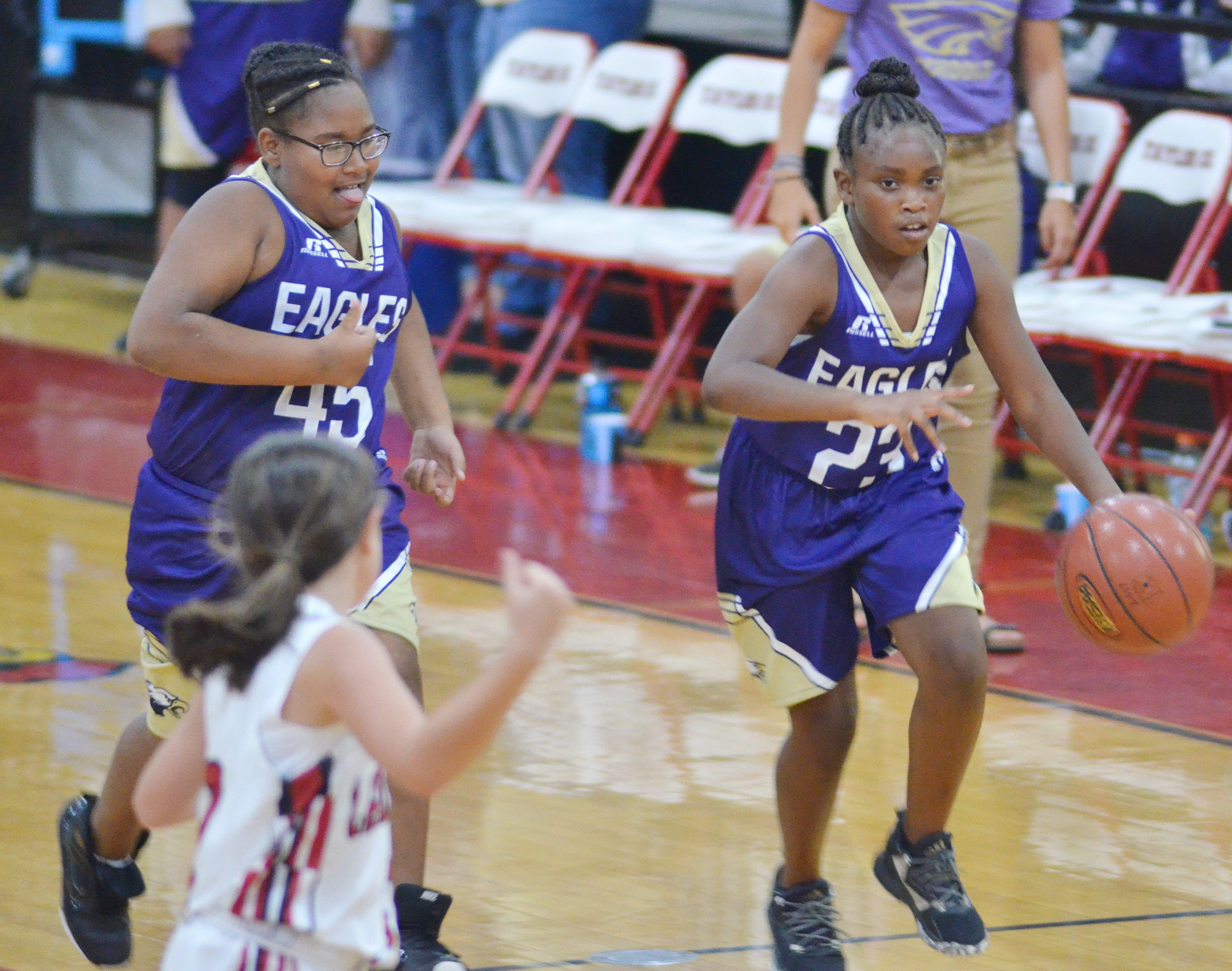 CMS sixth-grader KyAshia Mitchell, at left, and Campbellsville Elementary School fifth-grader Ta'Zaria Owens run to the basket.
